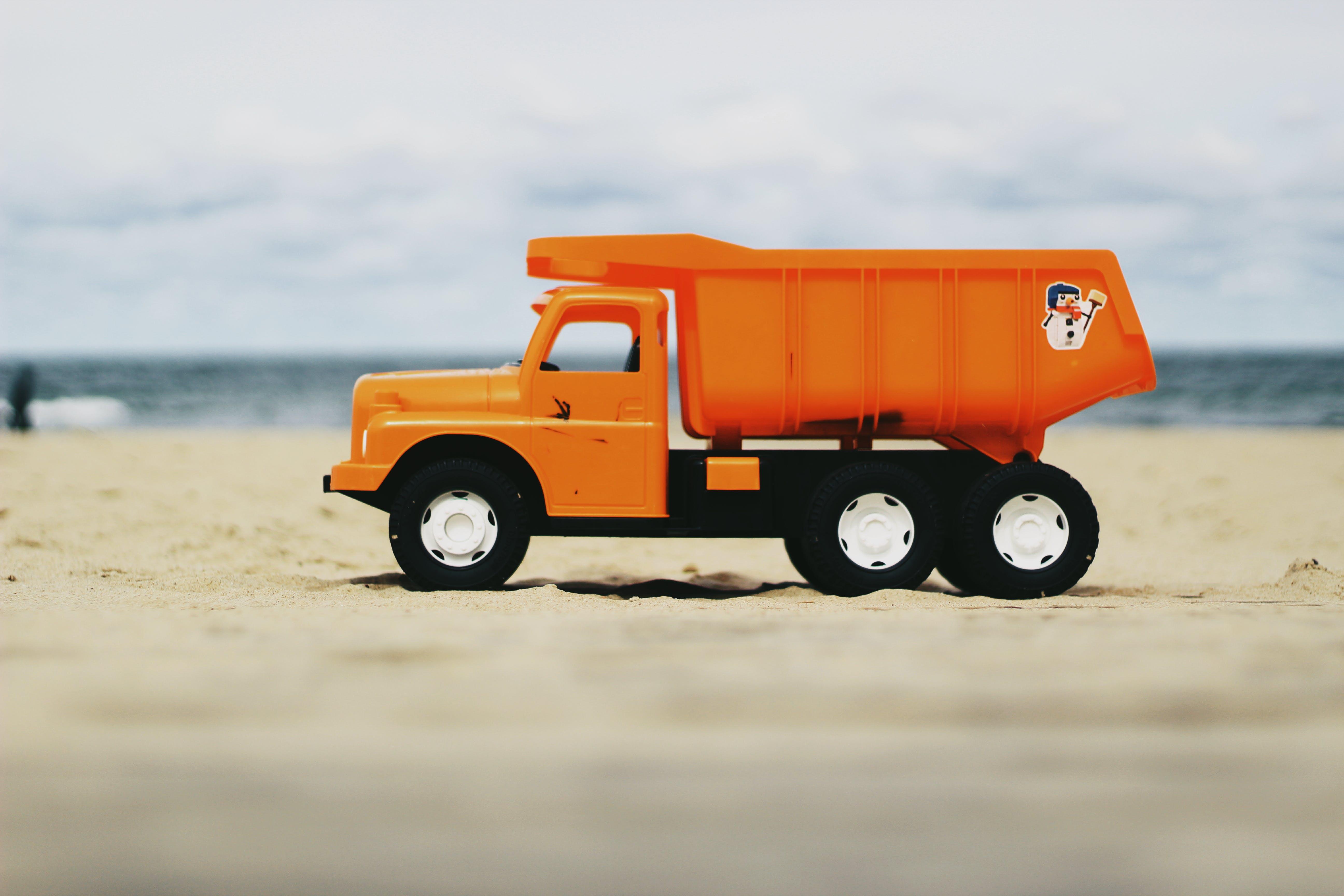 Kostenloses Stock Foto zu orange, spielzeug, spielzeuglastwagen, plastikspielzeug