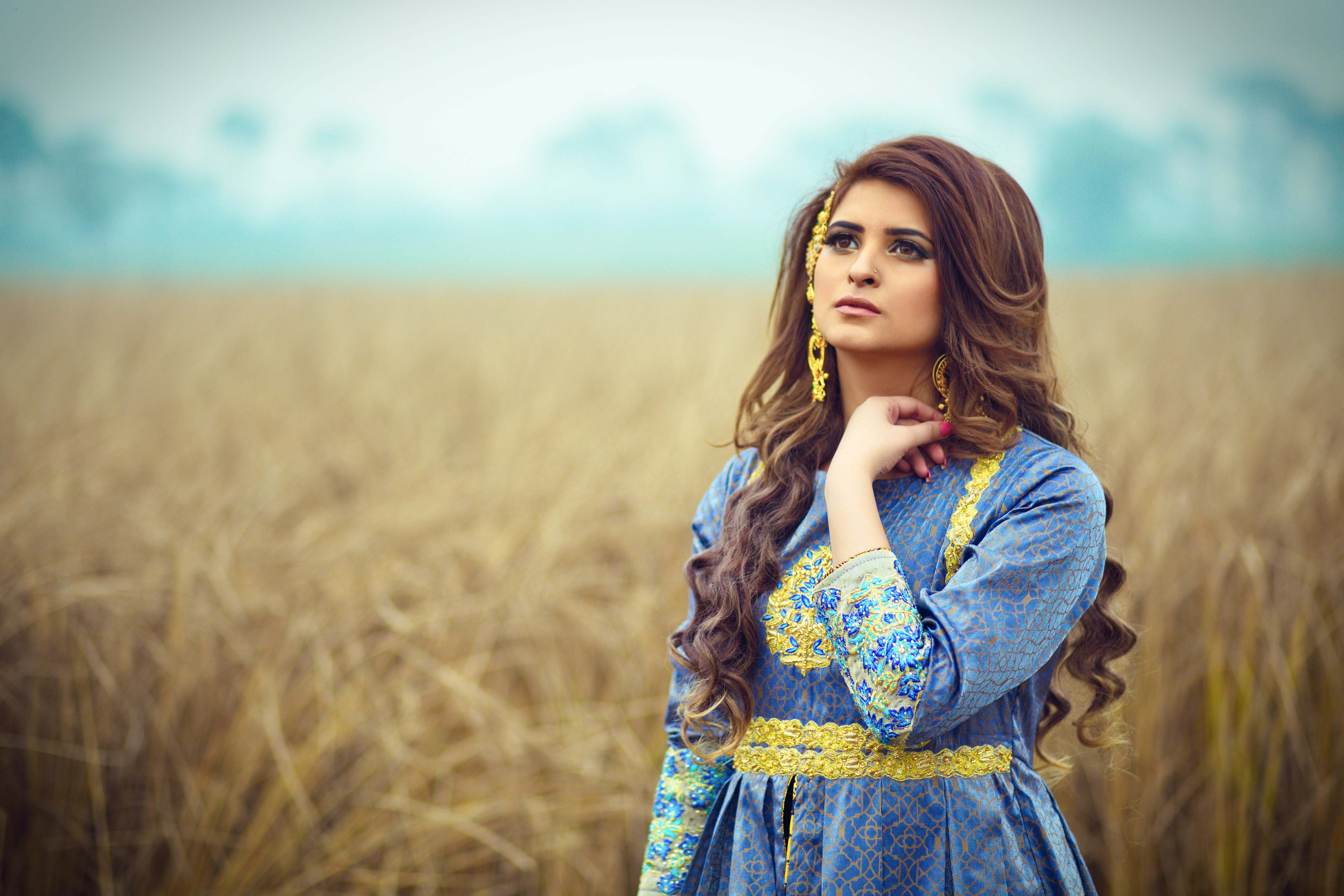 Brunette Haired Woman in Blue Dress Stranding in an Open Field