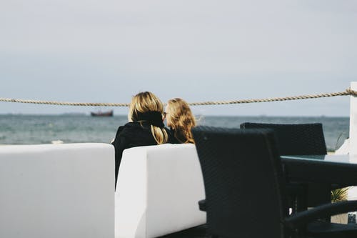 Two Women Sitting Near Body of Water