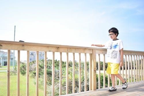Boy Walking on Wooden Bridge.