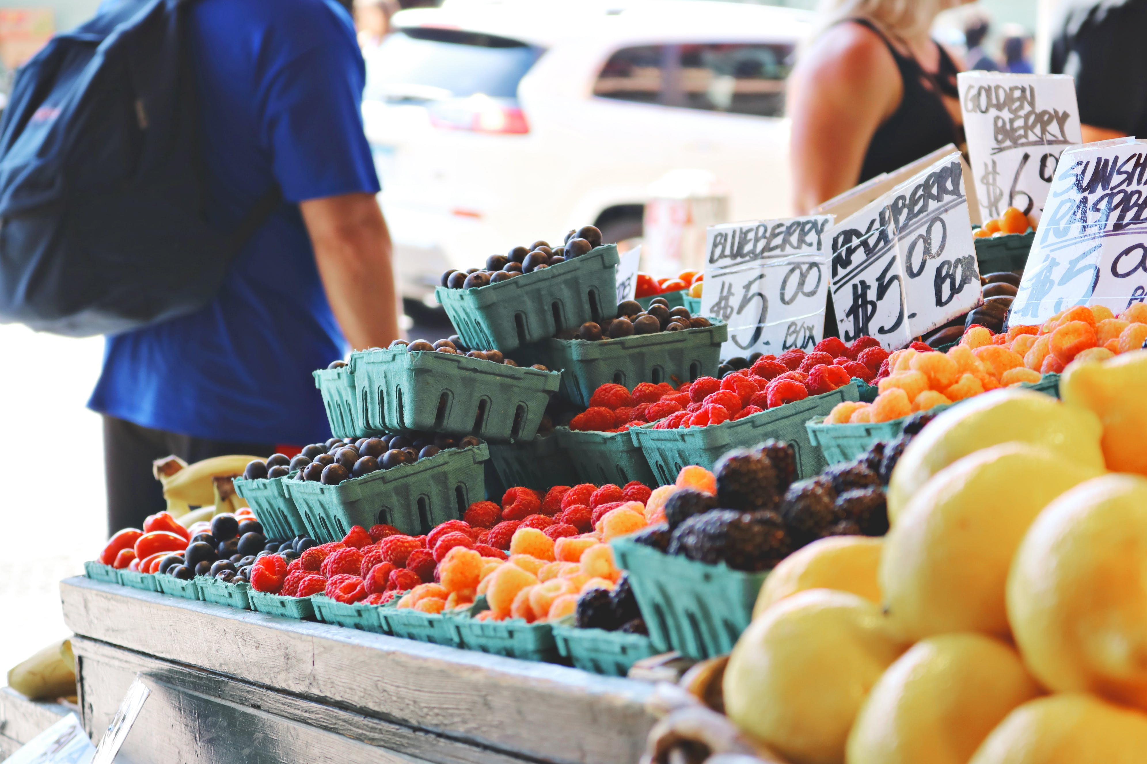Man Wearing Blue Top and Black Bottom Standing Near Fruit Stand