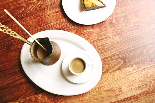 Top view of ceramic plate with copper cezve and cup of tasty coffee near yummy dessert on wooden table in apartment