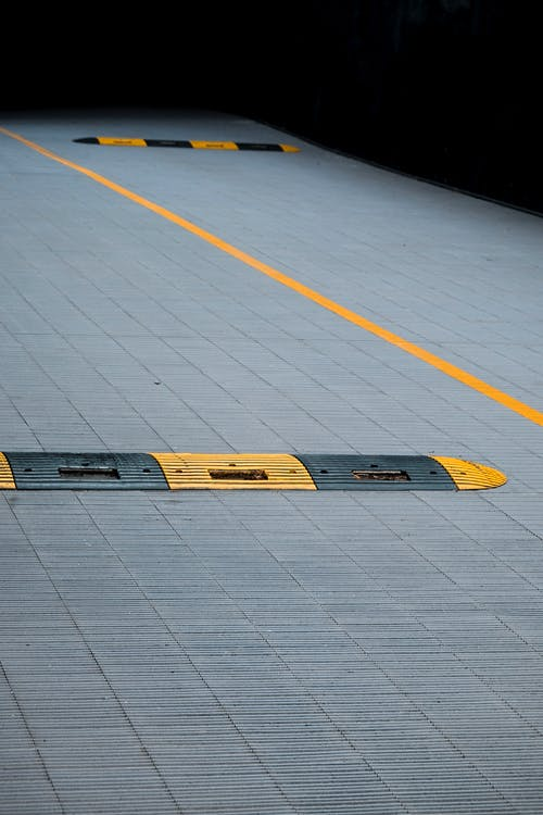 Yellow and Black Plastic Humps on Gray Concrete Floor