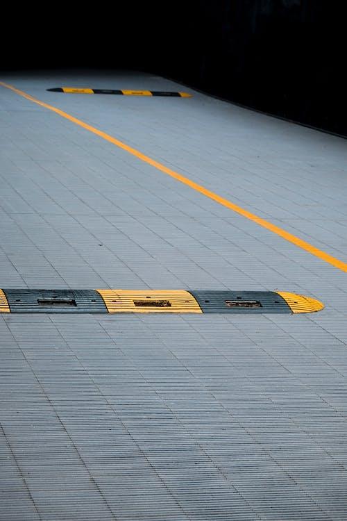Yellow and Black Plastic Humps on Gray Concrete Floor