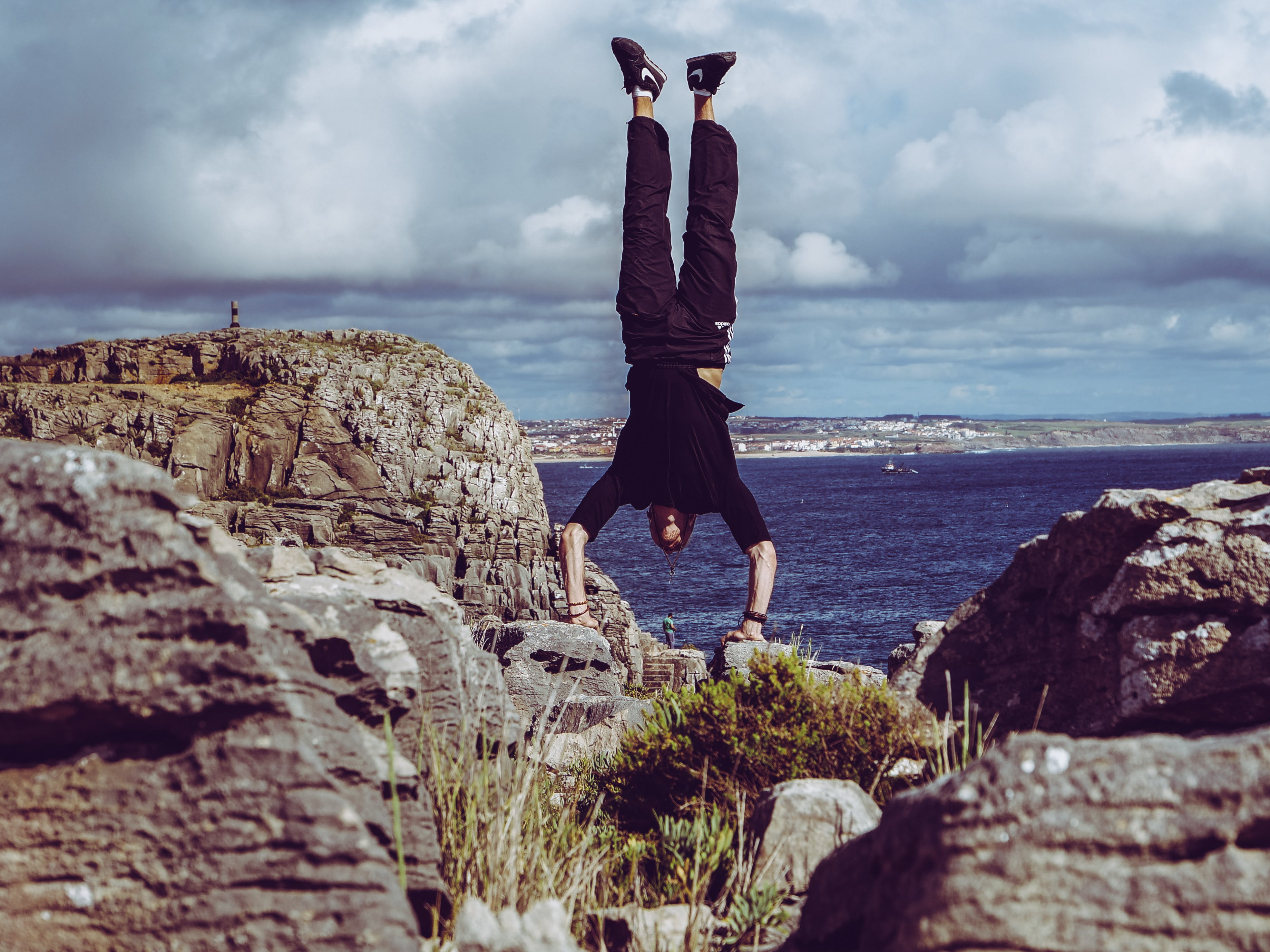 Man Wearing Black Dress Shirt and Burgundy Pants Hand Standing on Rock Formations Across Sea