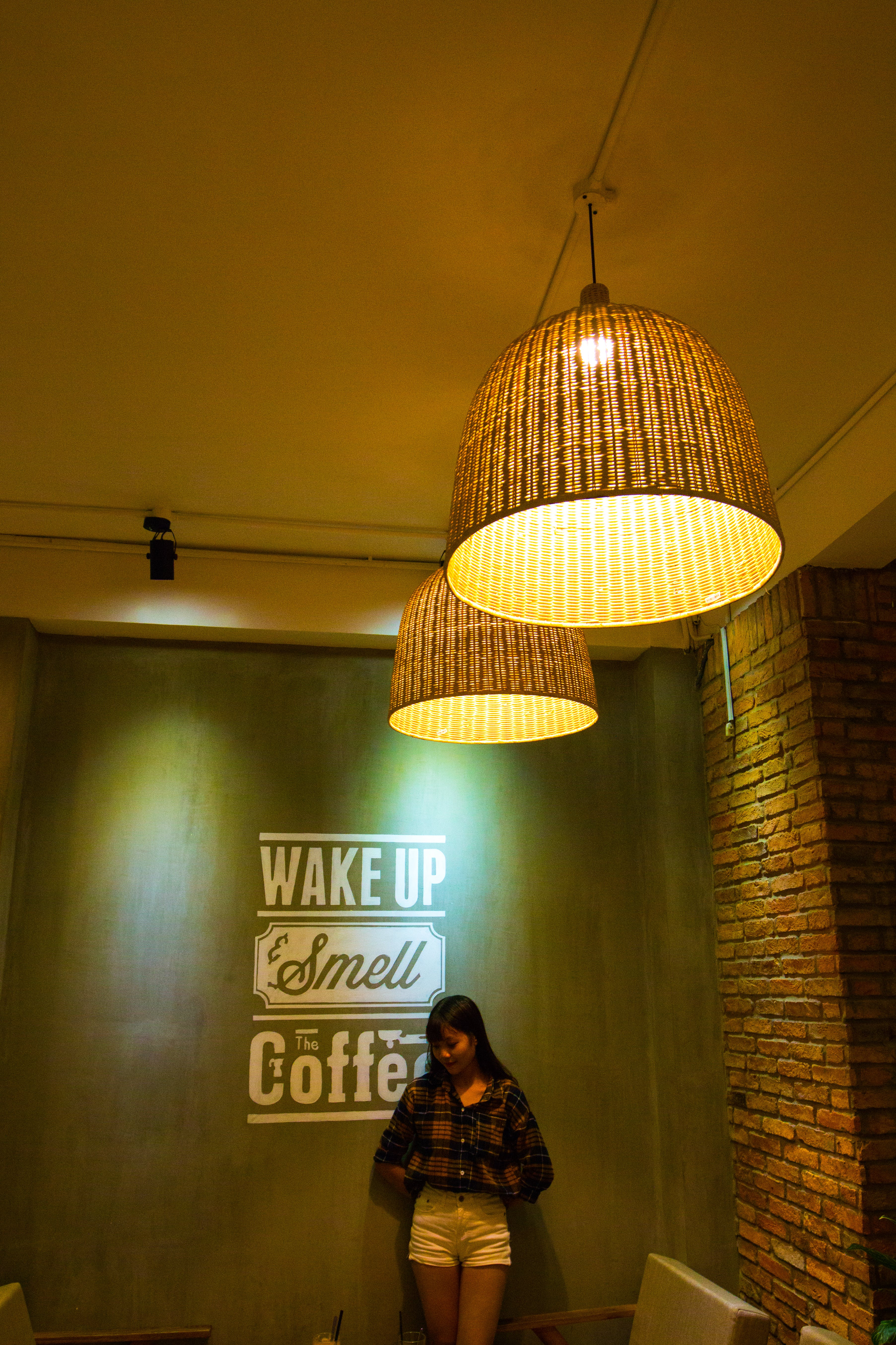 Woman Standing and Leaning Beside Wake Up Smell the Coffee Text Wall