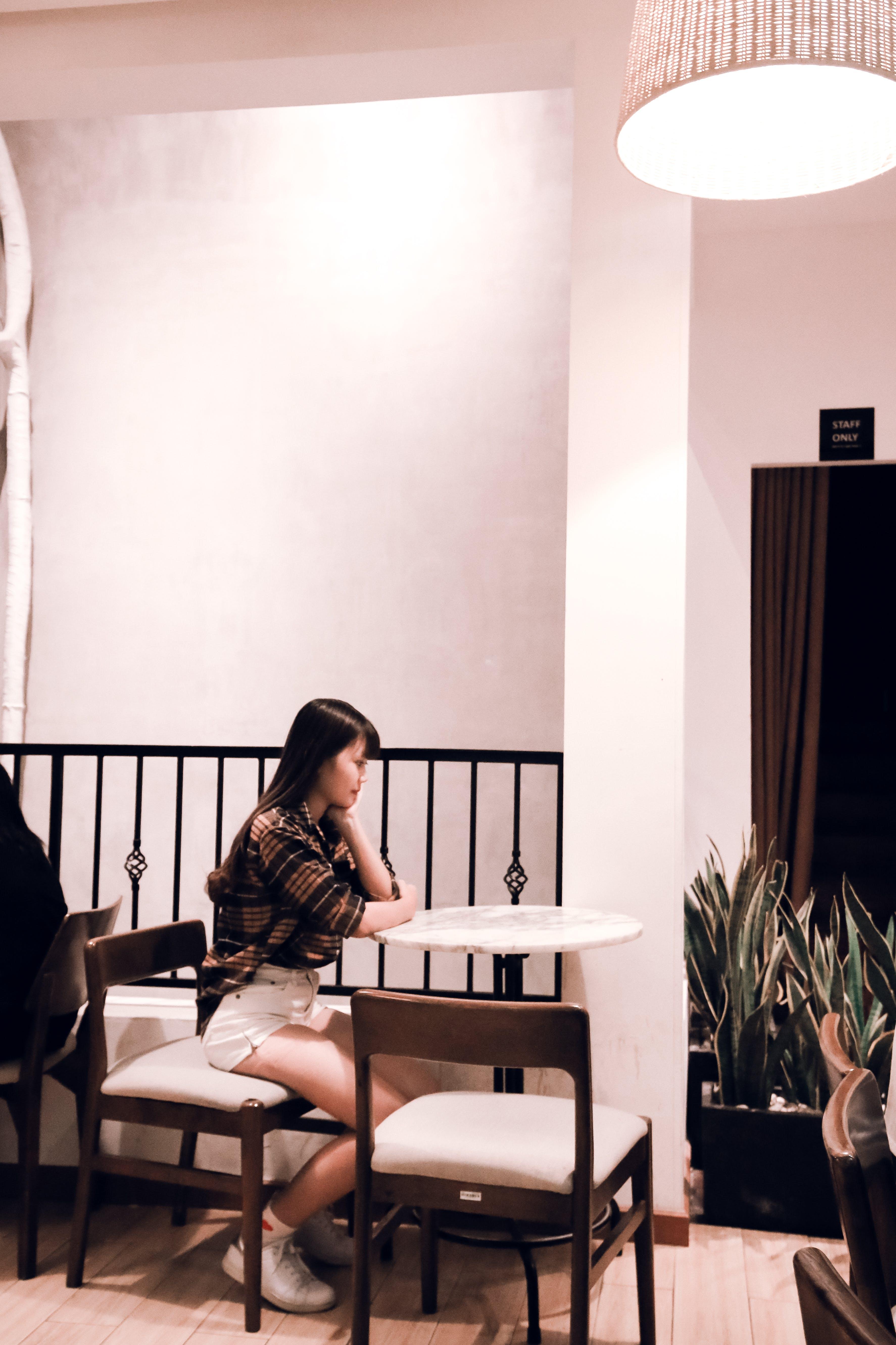 Sitting Woman Wearing White Short Shorts and Long-sleeved Shirt