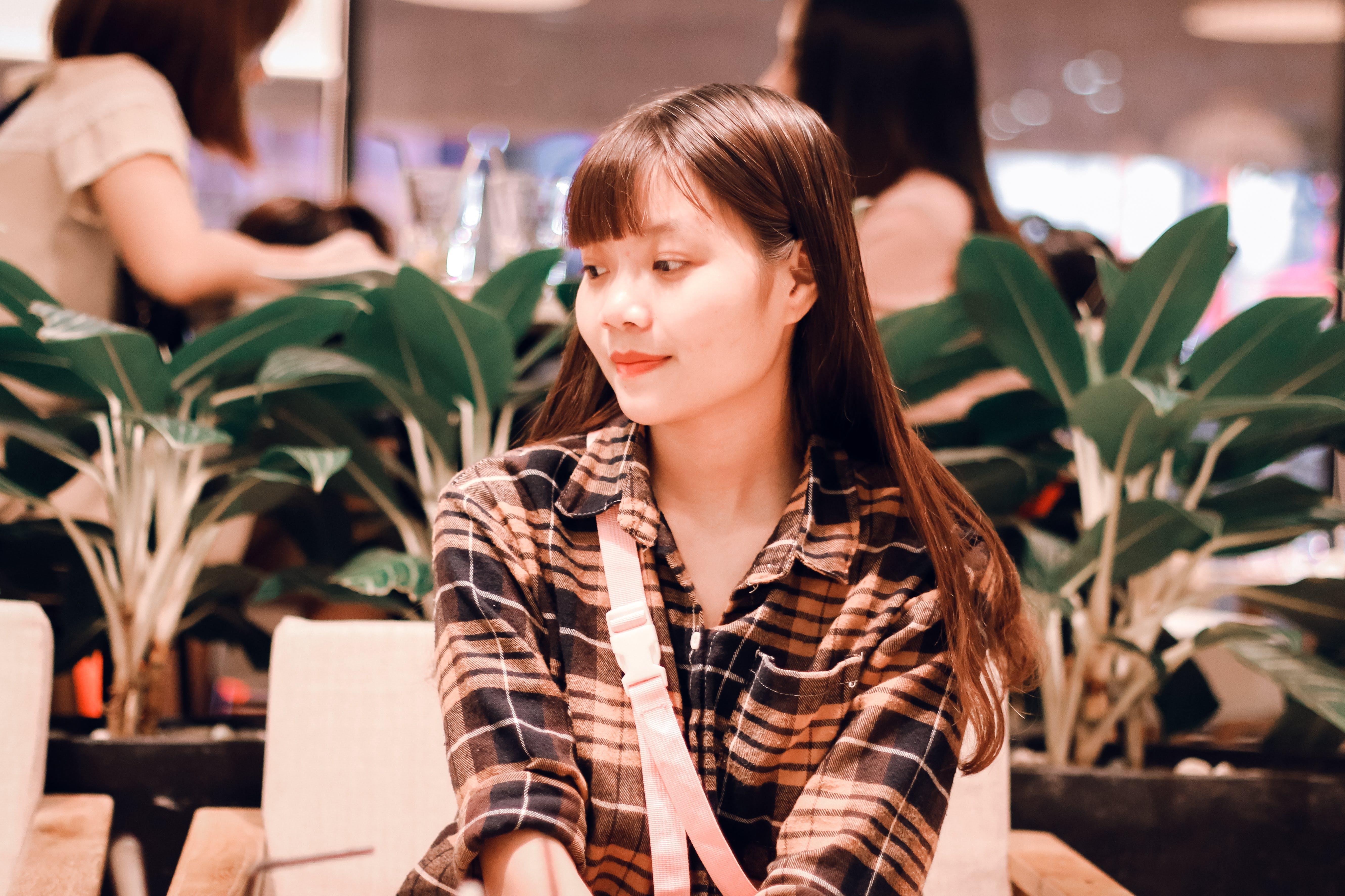Woman Wearing Black and Brown Plaid Sport Shirt Sitting on Sofa