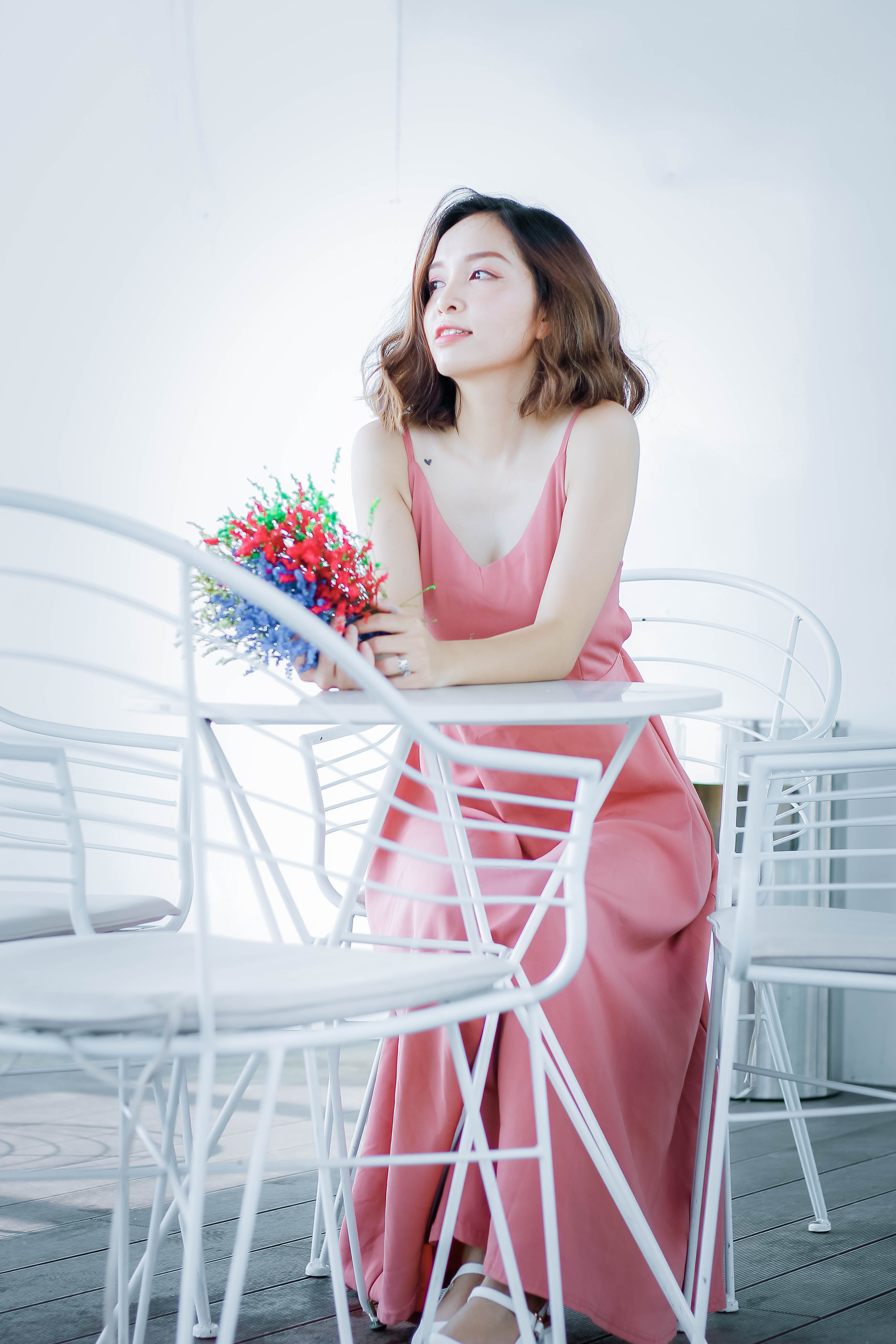Woman in Pink Dress Sitting on Chair