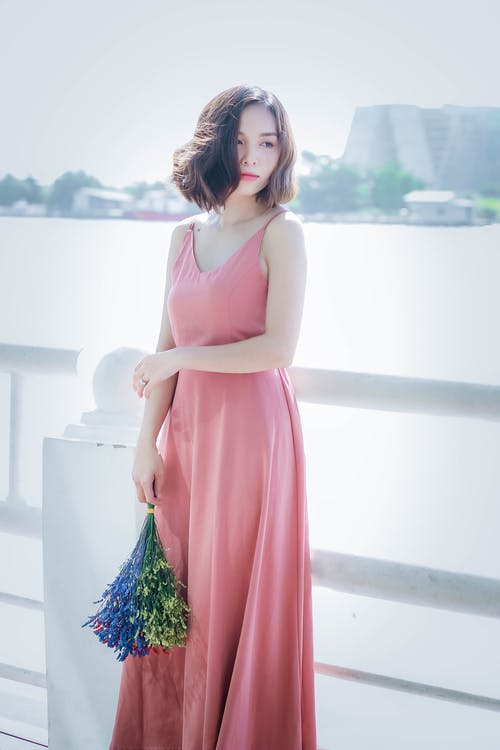 Woman Wearing Pink Spaghetti Strap Maxi Dress Holding Flowers