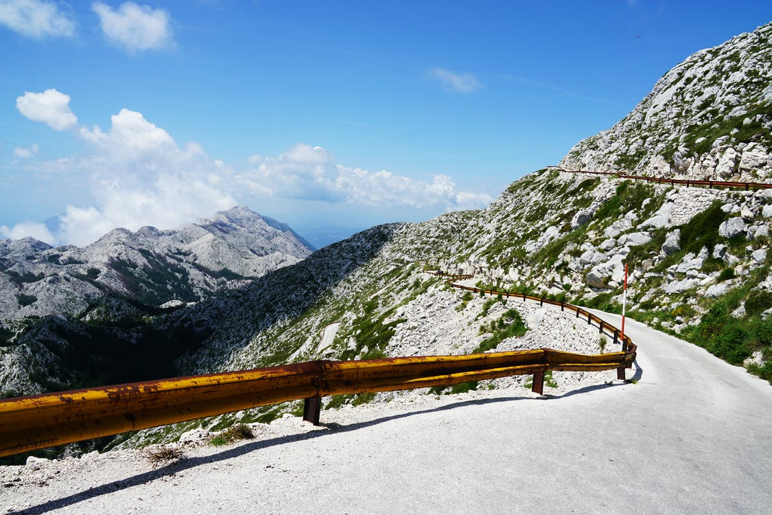 Photo of Narrow Paved Mountain Road with Barrier.