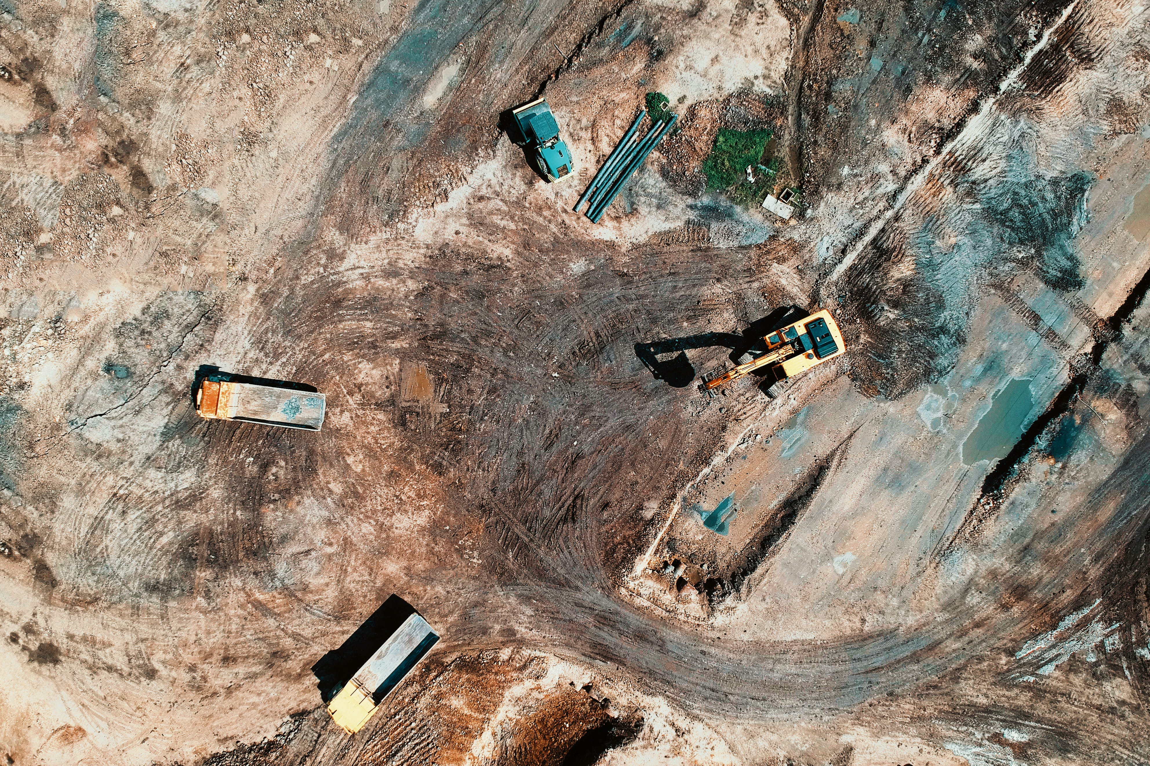 Aerial View Photography Of Utility Vehicles On Brown Soil
