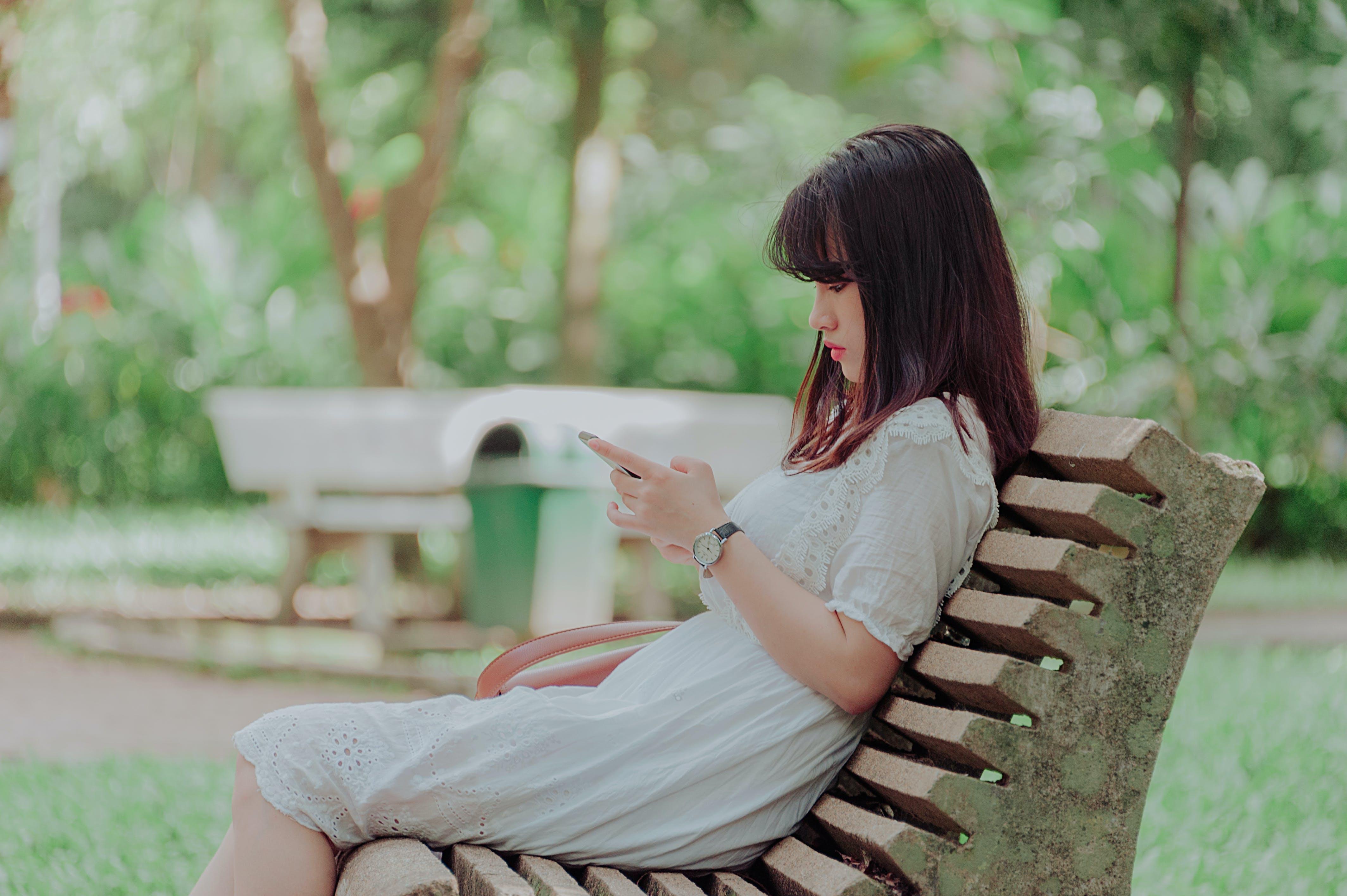 Woman Wearing White Dress Sitting on Bench
