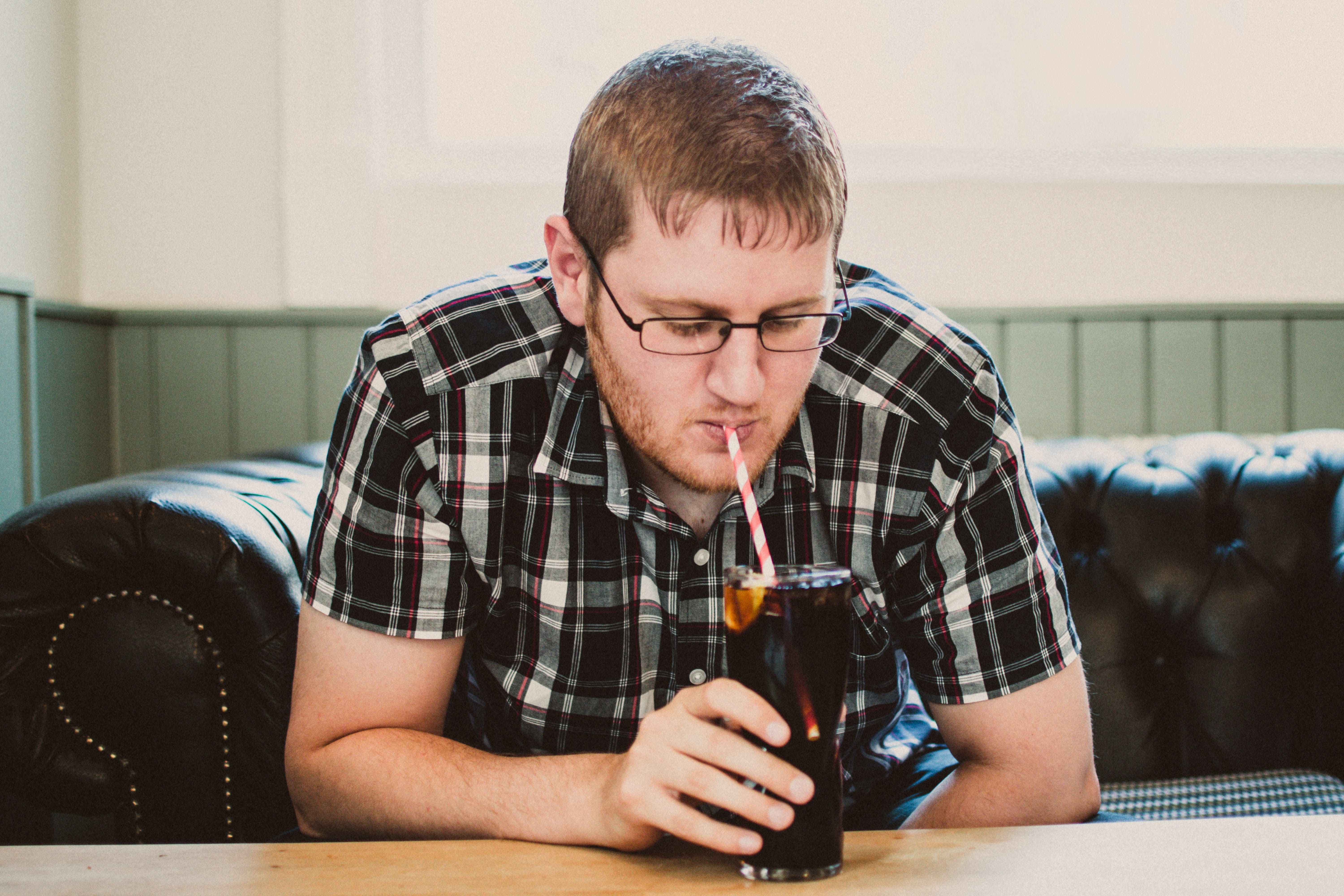 Man Sipping Drink From Clear Glass