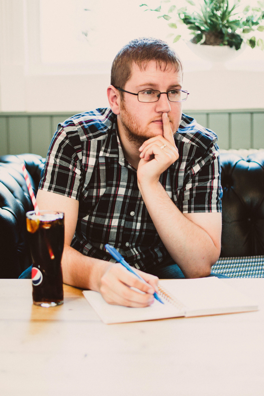 Man Wearing Black Plaid Shirt Sitting