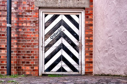 Free stock photo of black and white, brick wall, door, geometric pattern