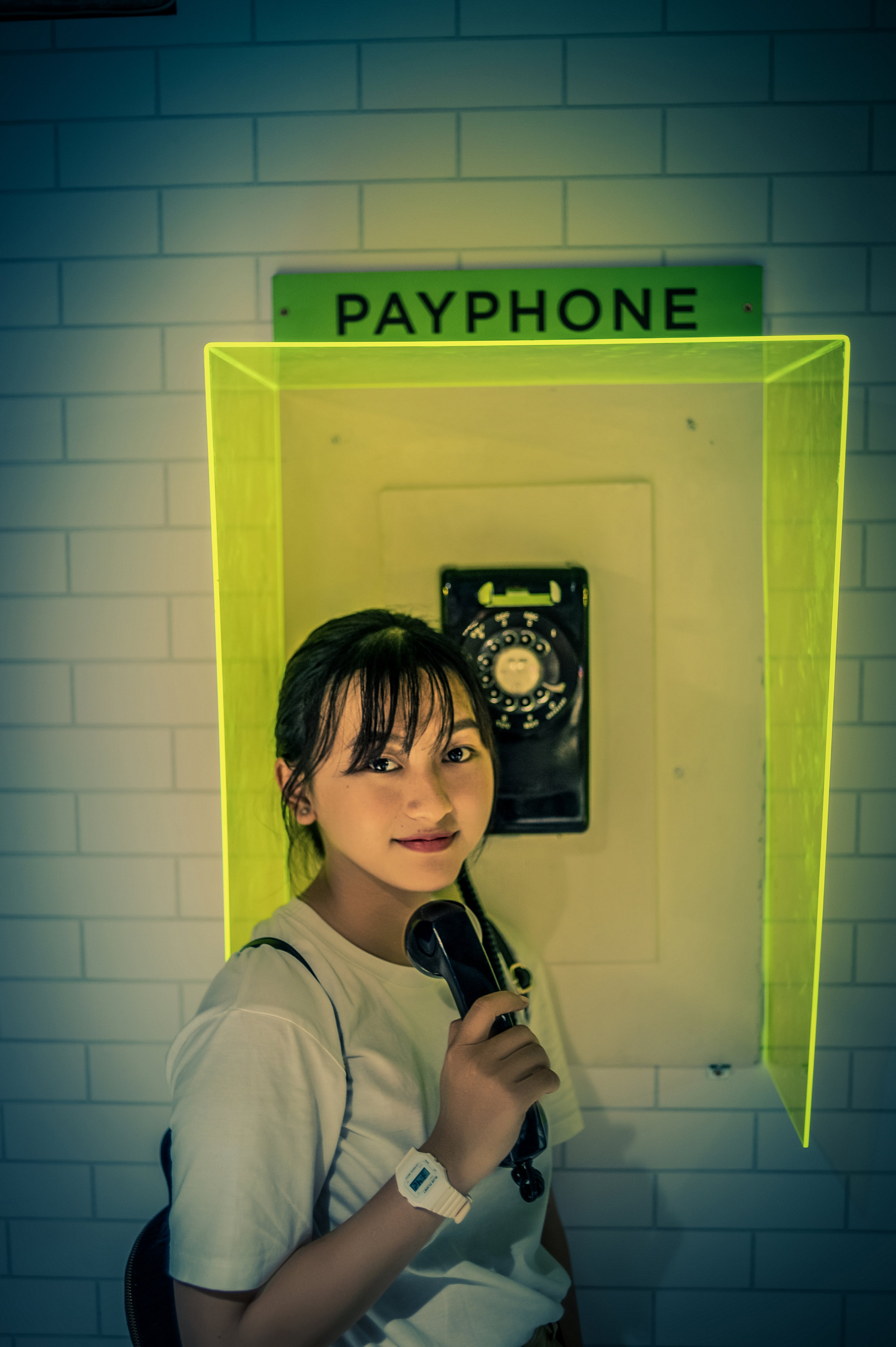 Photo of Woman Standing Beside Payphone.