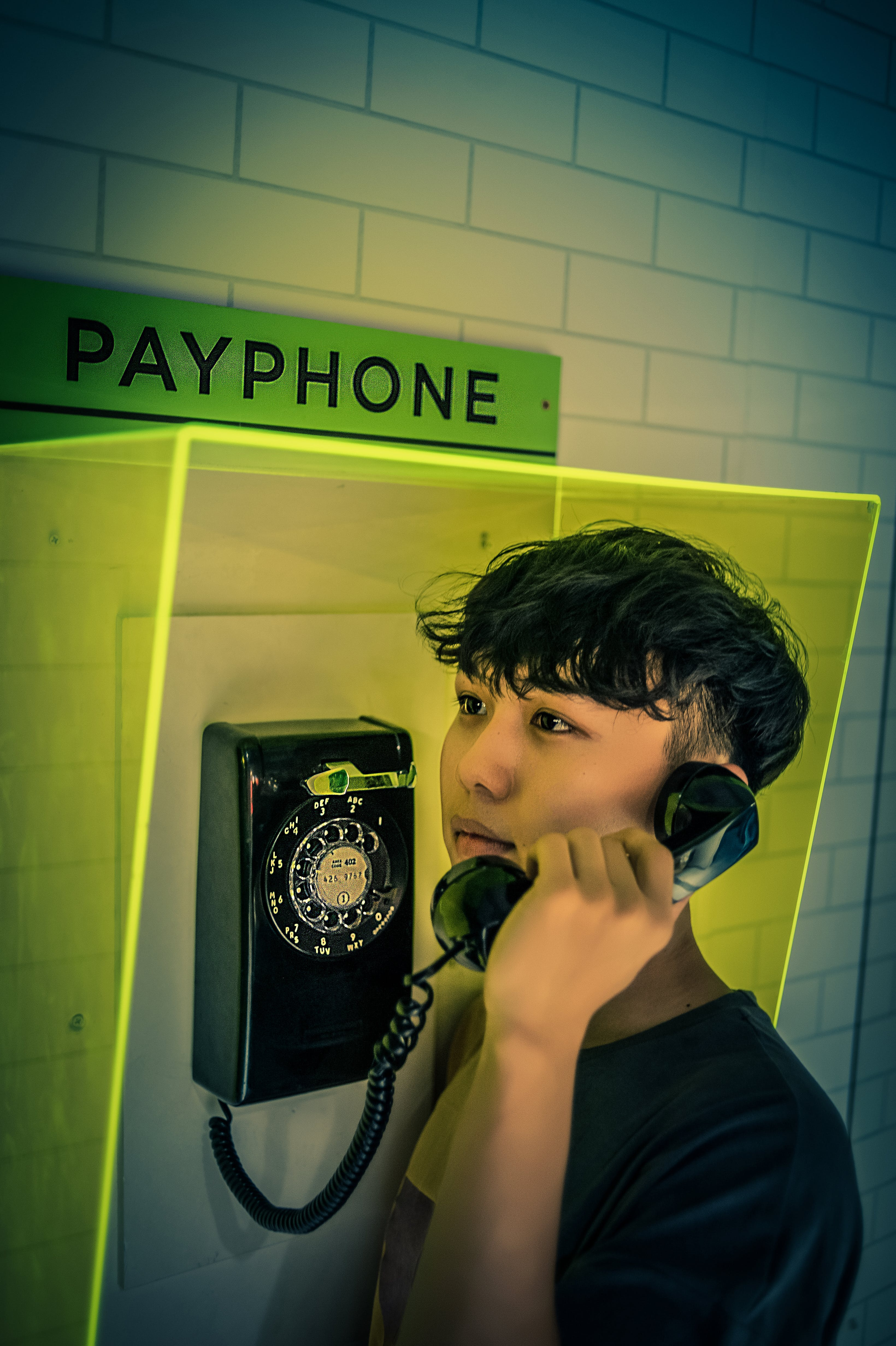 Man Holding Black Rotary Payphone