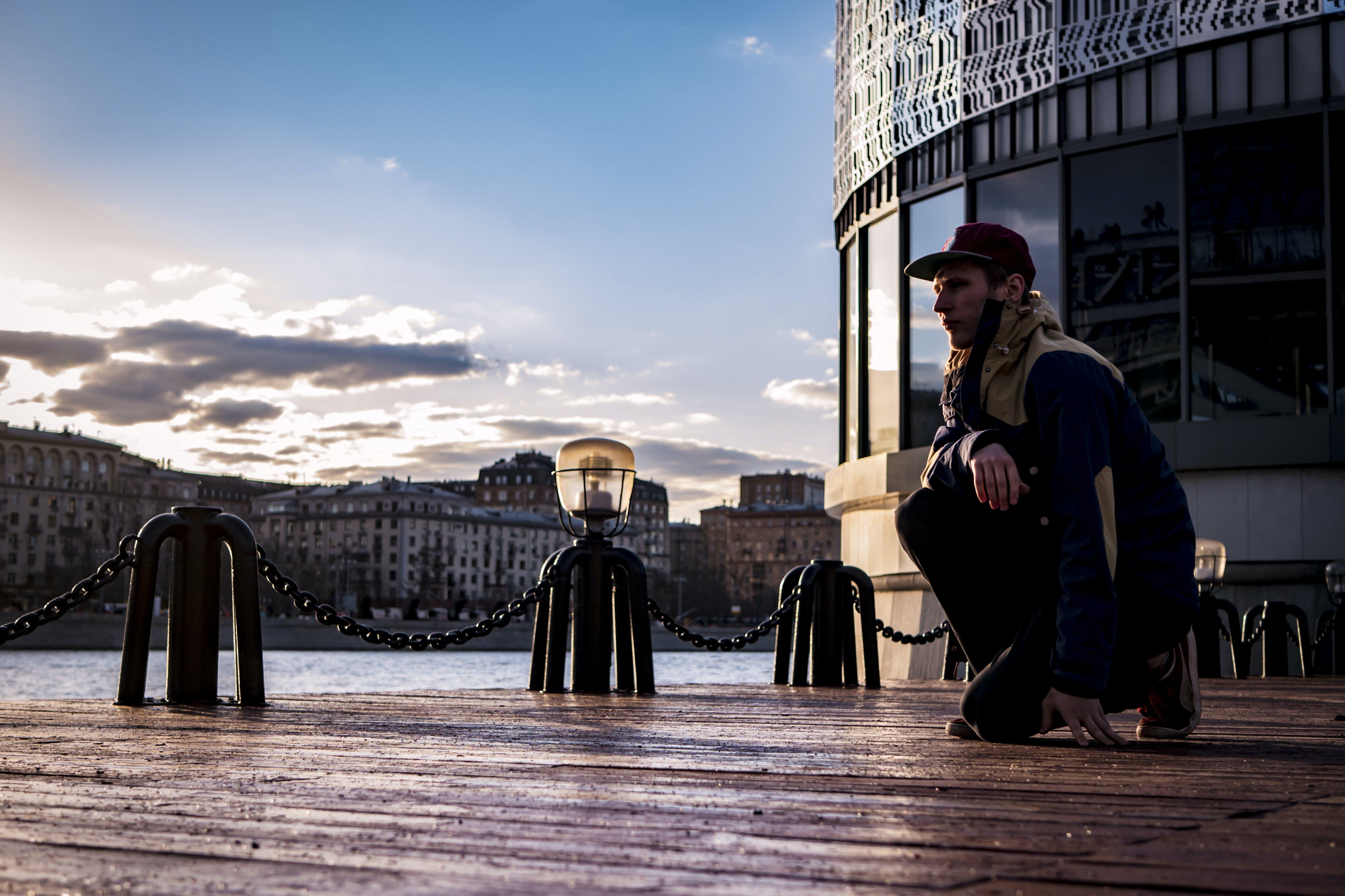 Man Kneeling in Front of Glass Building