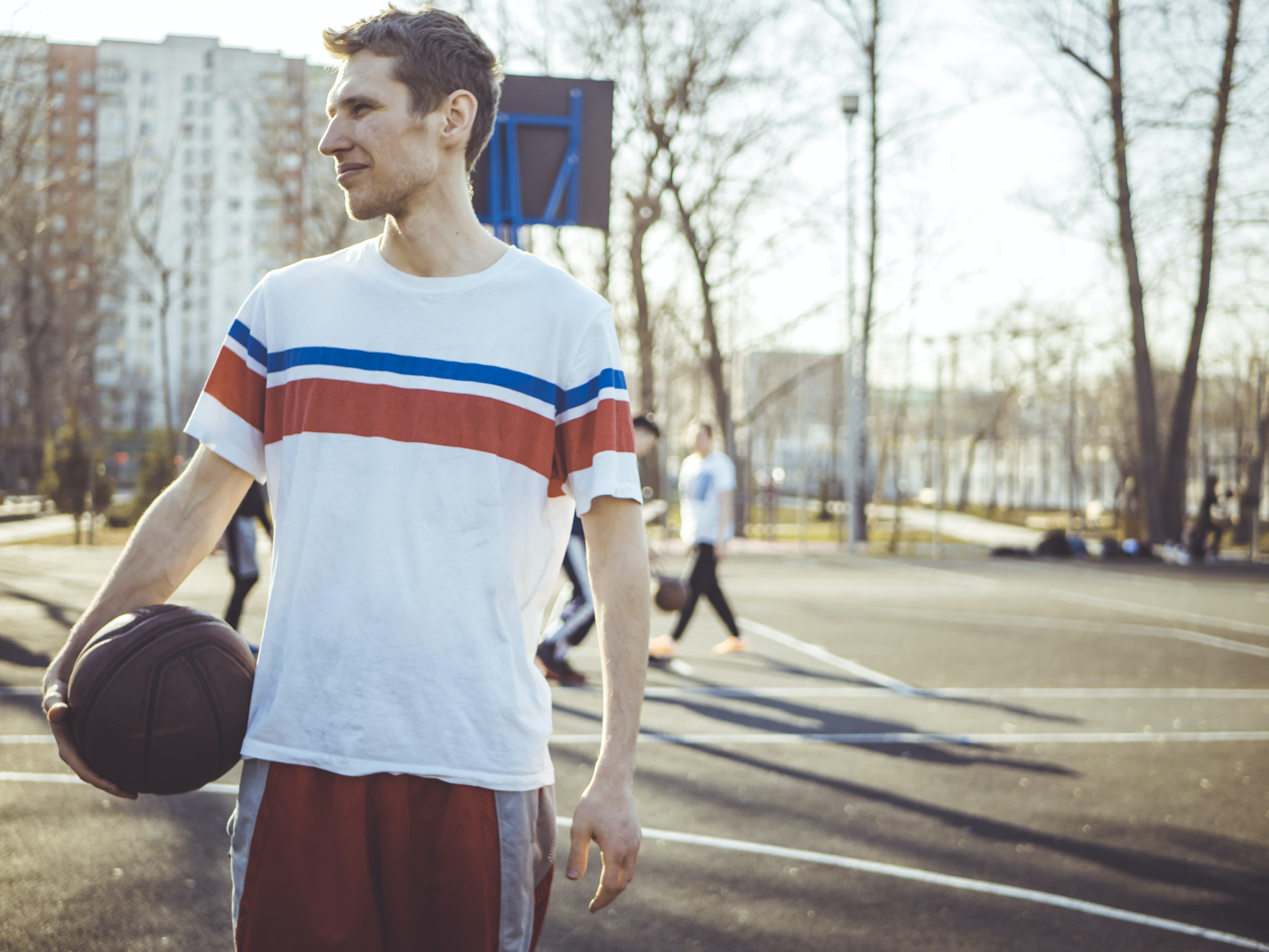 Man Wearing Shirt Holding Basketball in Court