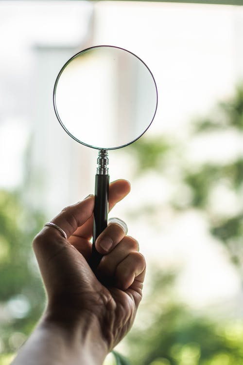 Tilt Shift Lens Photography of Person Holding Magnifying Glass