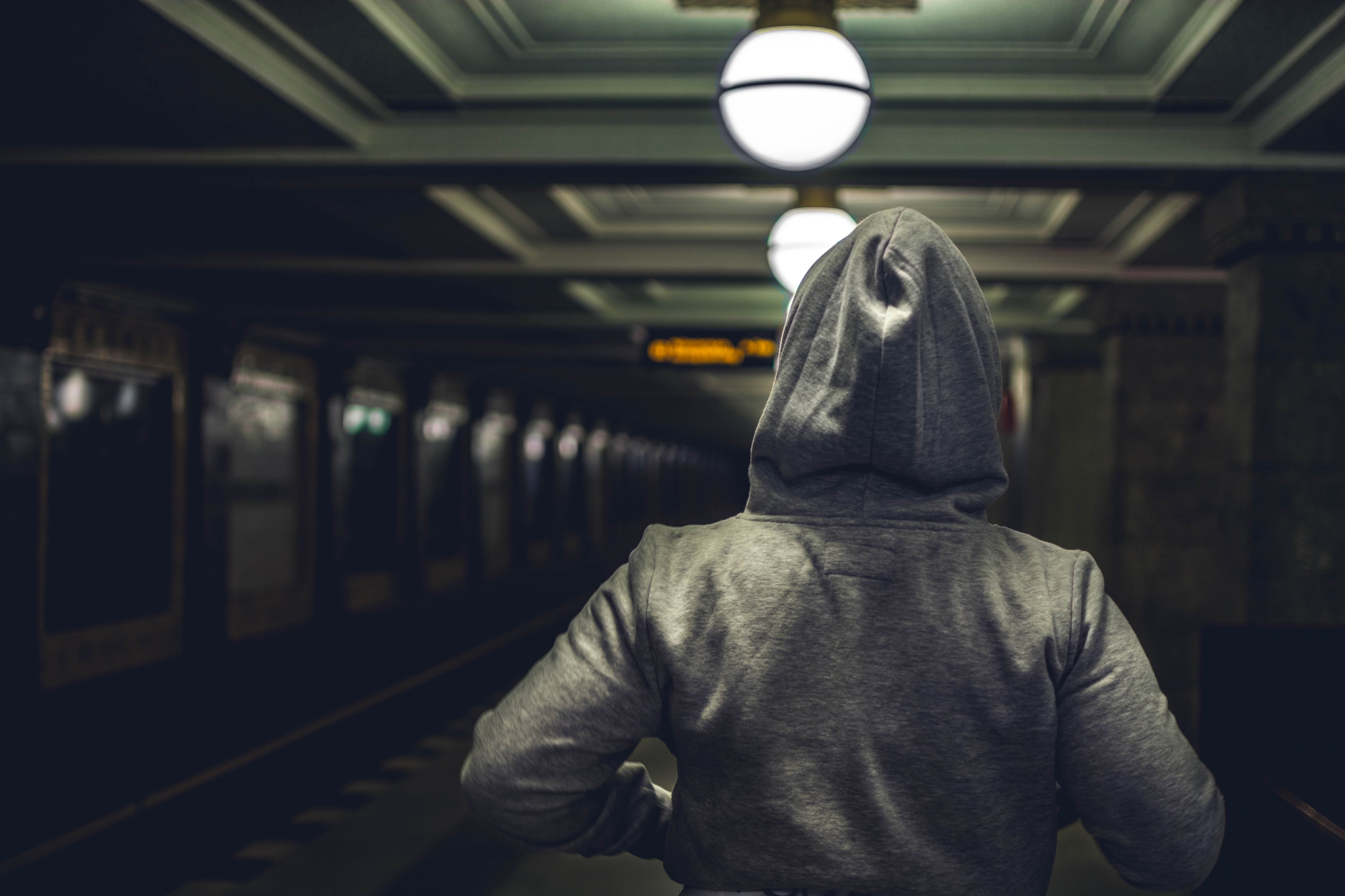 Person Wearing Gray Hooded Jacket in Train Station