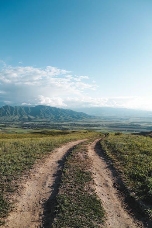 alan, asfaltsız yol, bulutlar, çayır içeren Ücretsiz stok fotoğraf