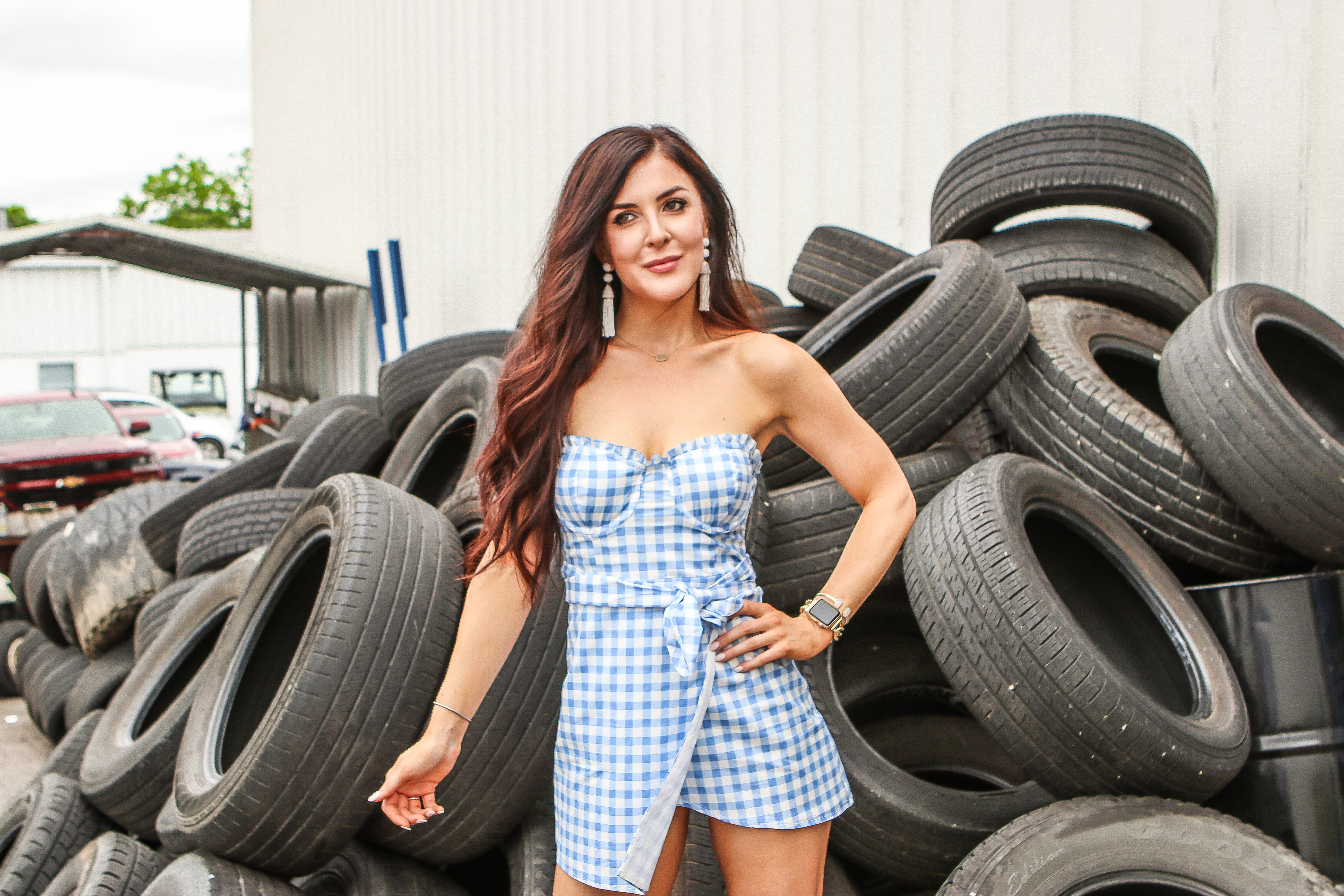 Woman in Blue and White Checkered Dress Standing in Front of Stack Tires