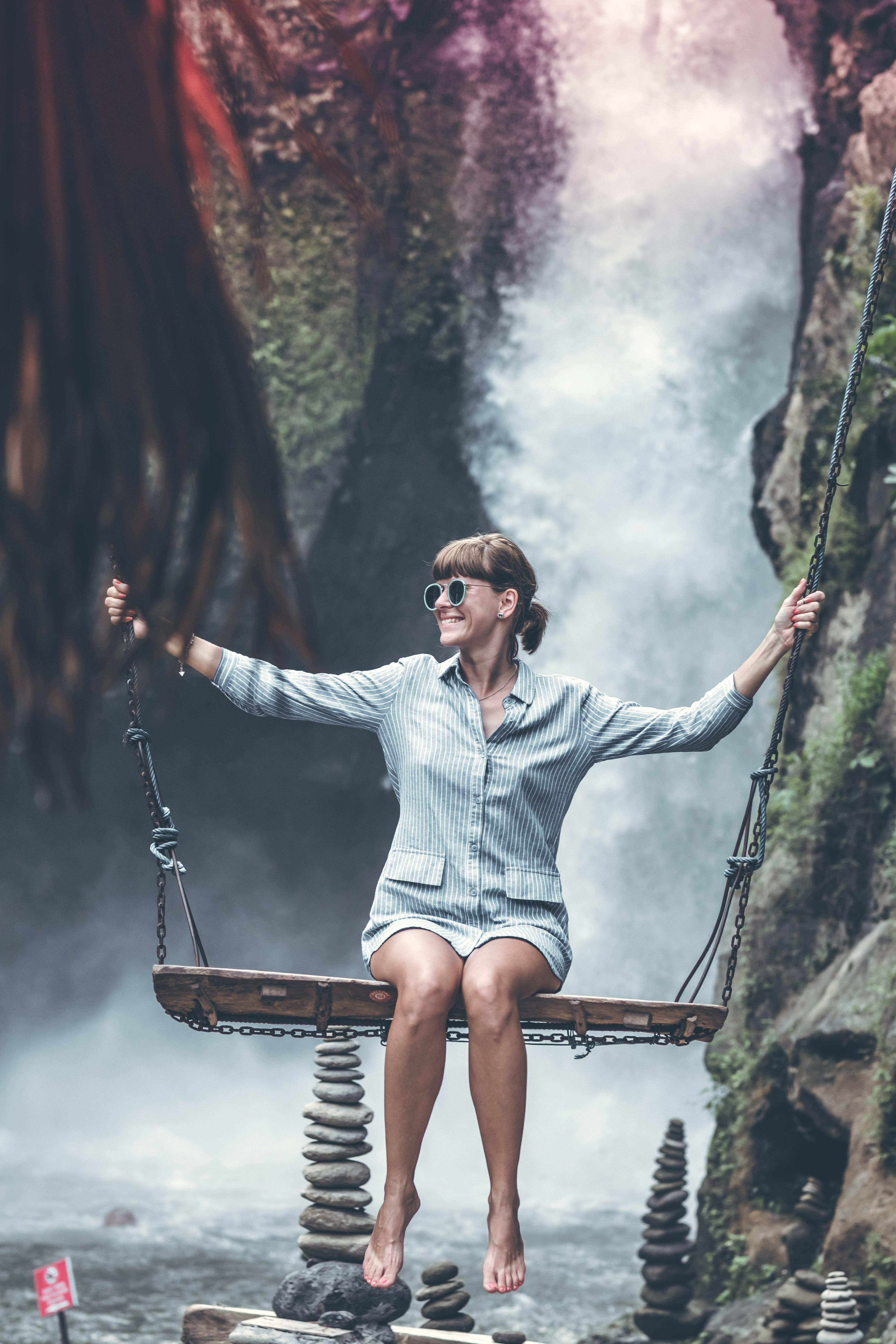 Woman Sitting on Swing Chair With Waterfalls Background