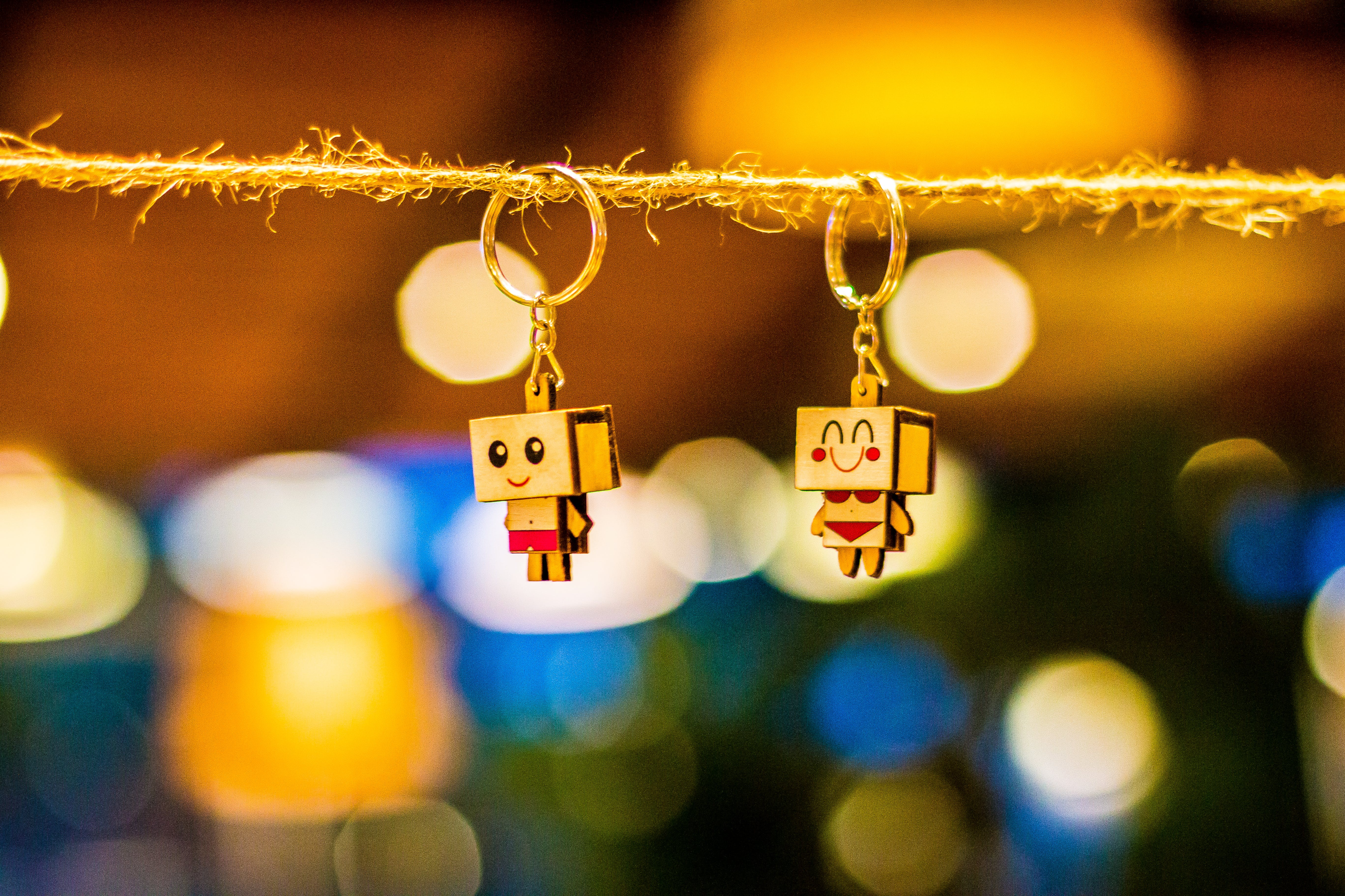 Two Brown Wooden Character Keychains Hanged on Brown Rope