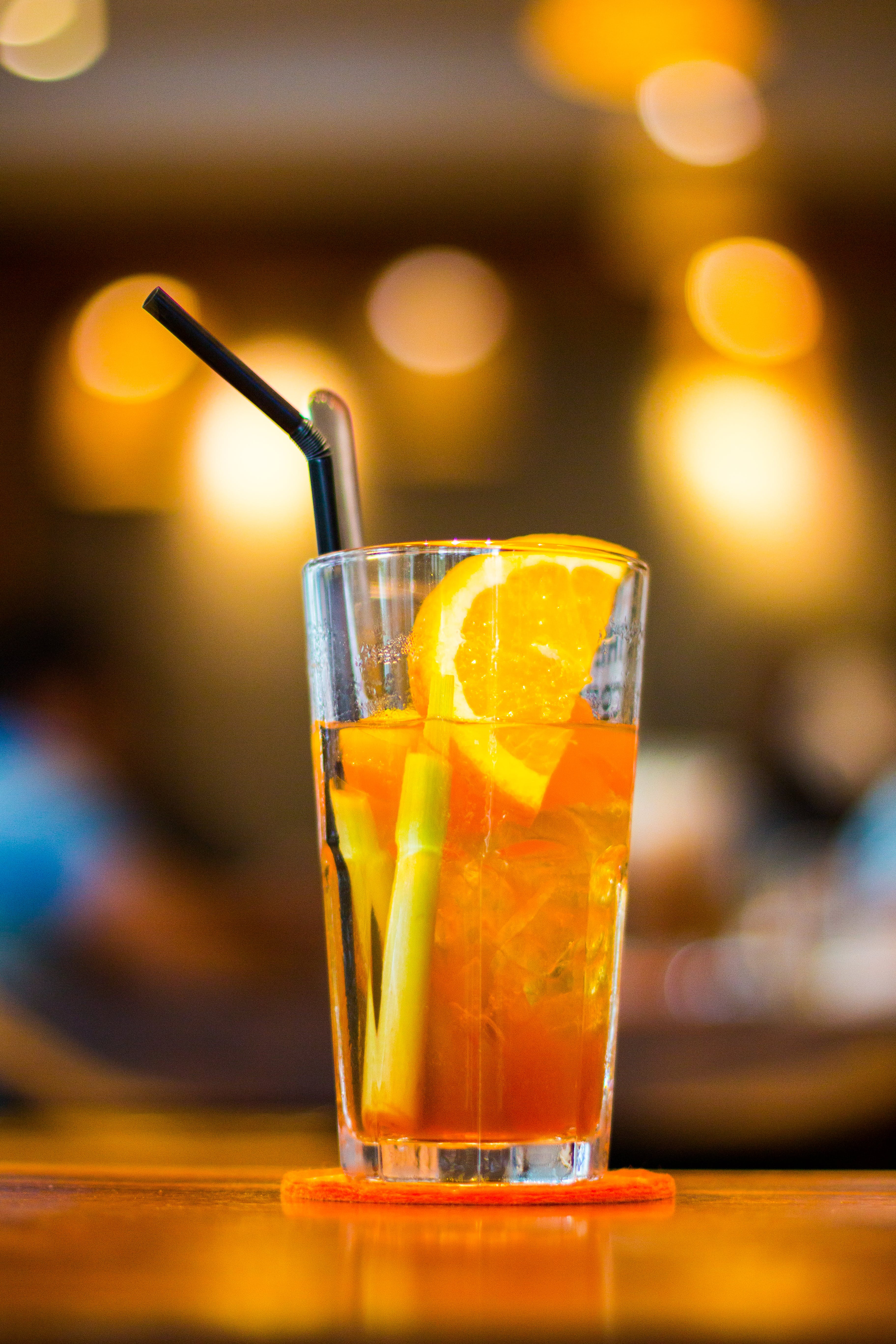 Clear Drinking Glass Filled With Orange Juice With Black Straw