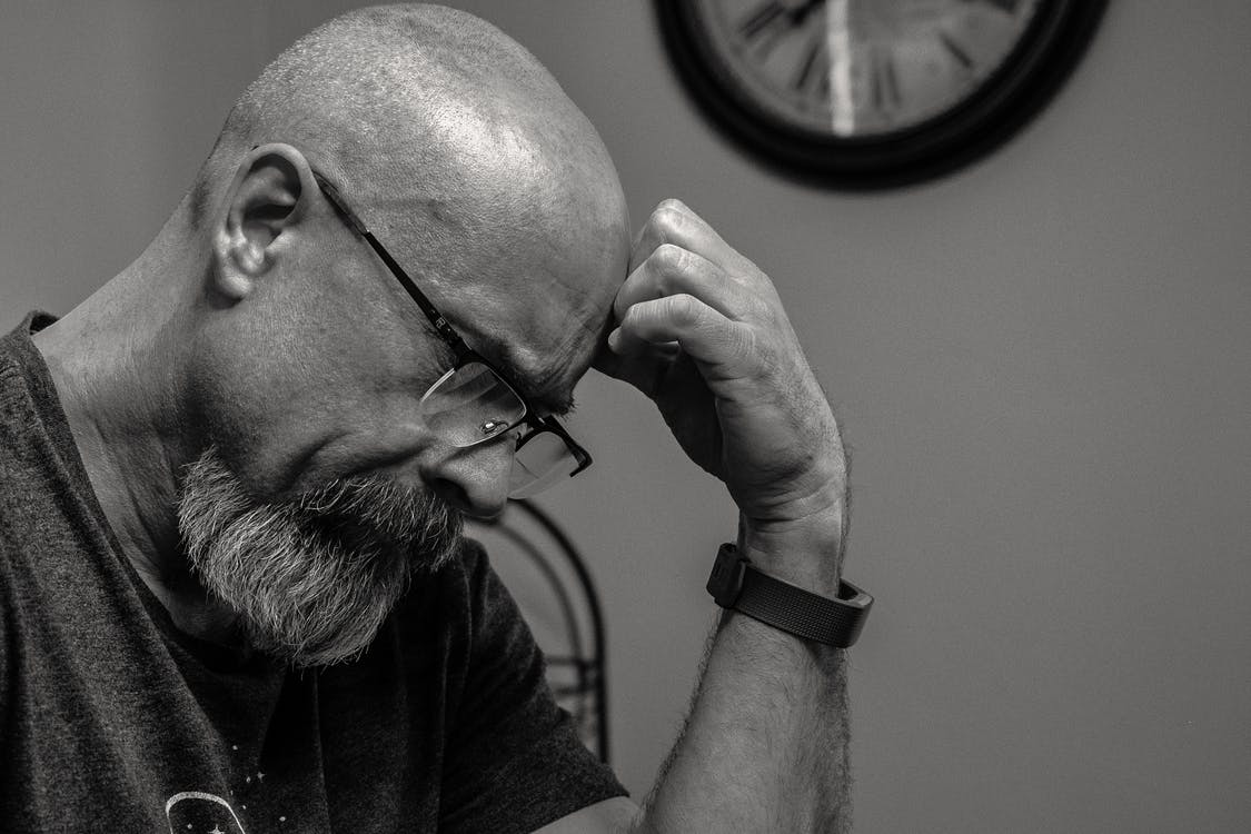 Grayscale Photo of Man Thinking in Front of Analog Wall Clock
