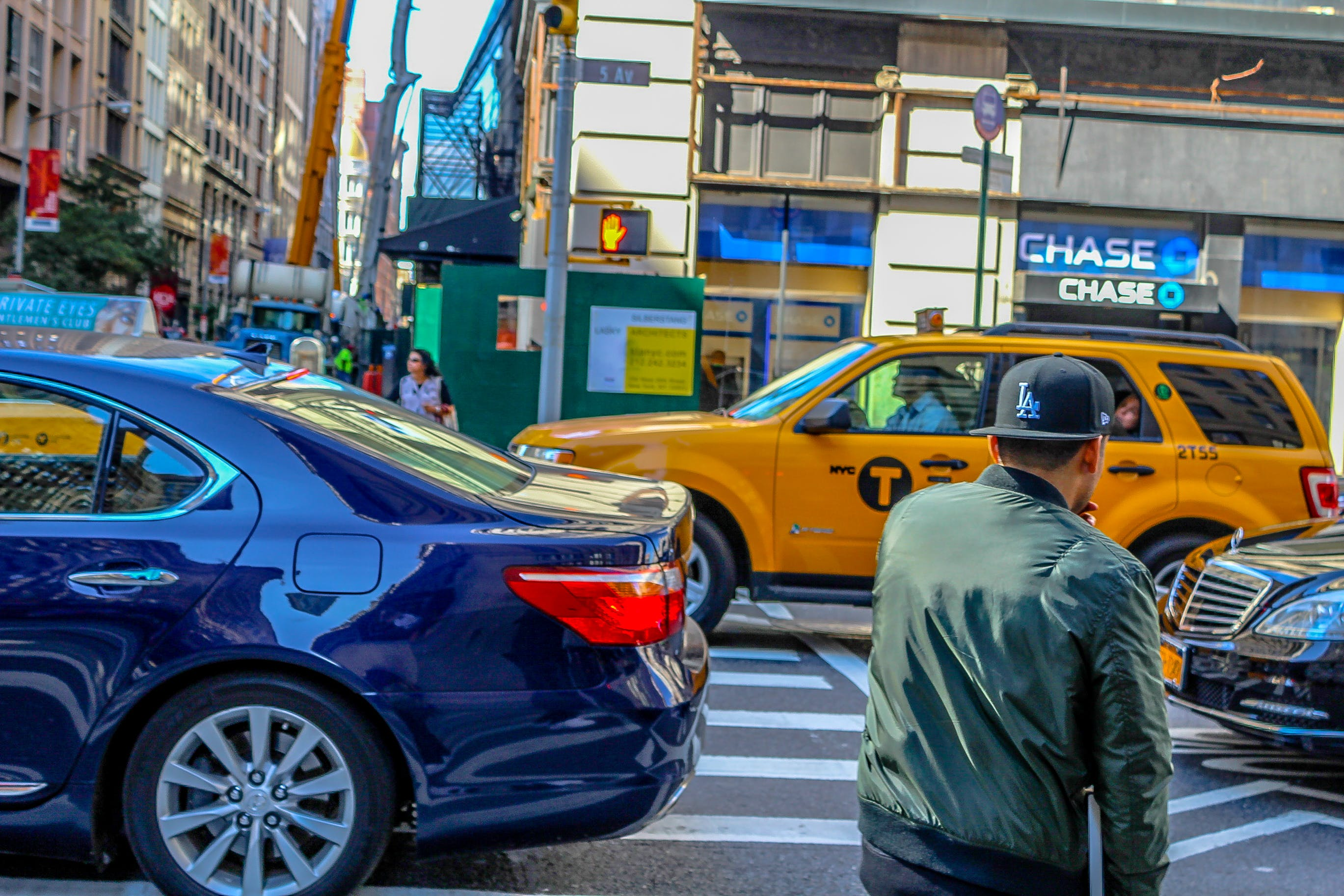 Man in Green Jacket Attempting to Cross on Pedestrian Lane With Vehicles Passing