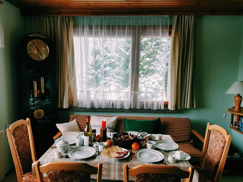 Arranged Table With Chairs and Plates Near Window