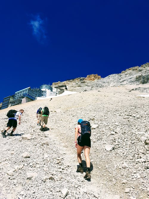 Group of tourists with backpacks climbing mountain under blue sky