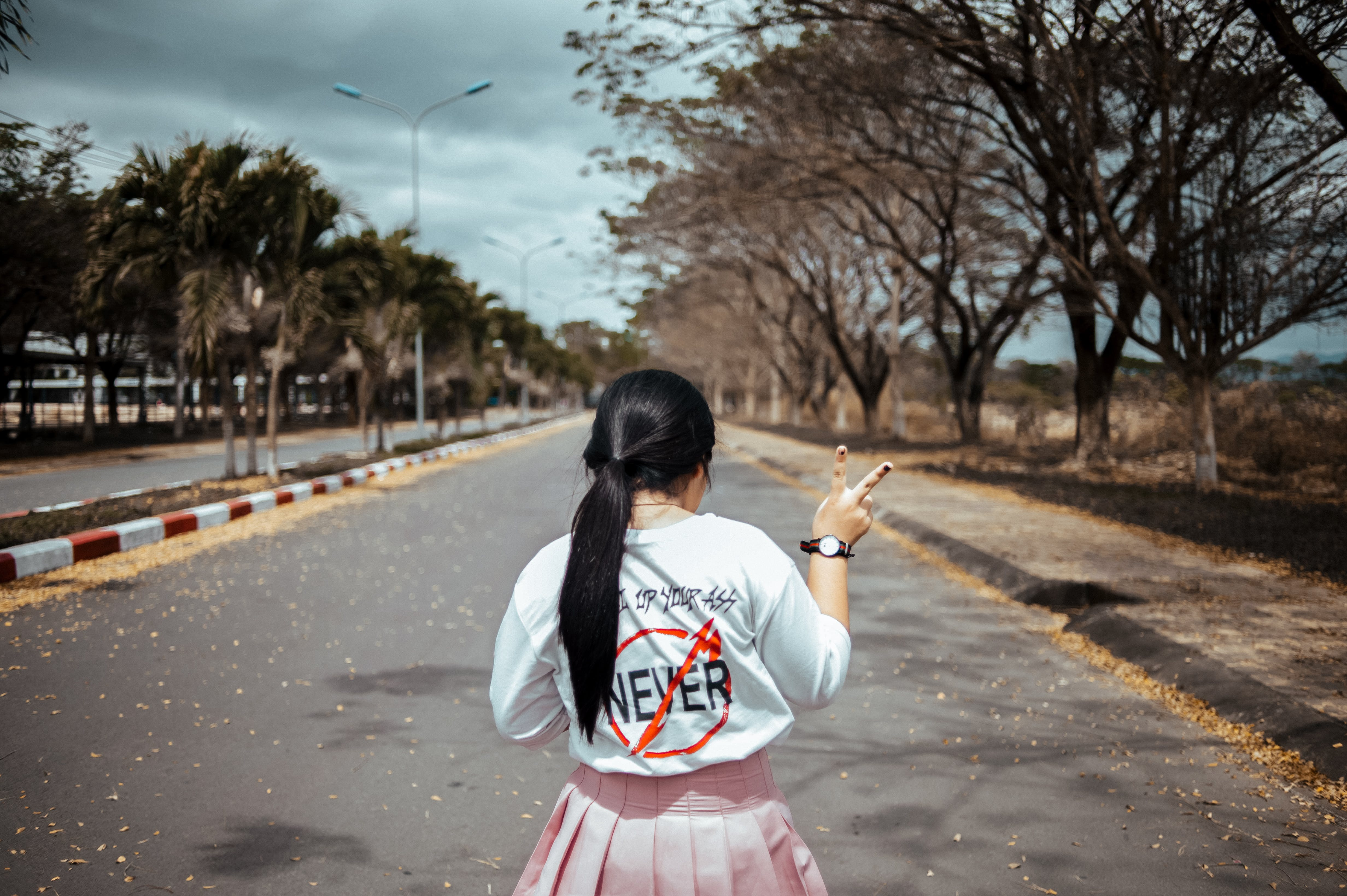 Woman Wearing White Long-sleeved Shirt and Pink Pleated Skirt Standing on Asphalt Road Between Green Trees Under Gray Sky at Daytime