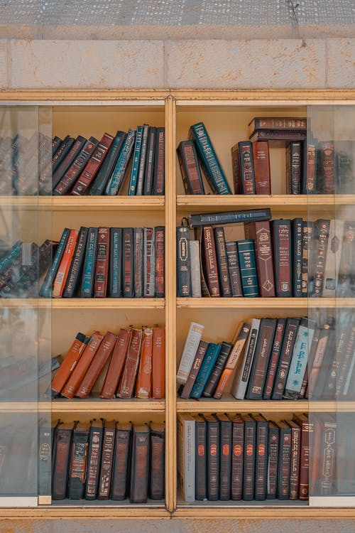 Assorted-title of Books Inside Brown Wooden Framed Glass Wall-mount Cabinet