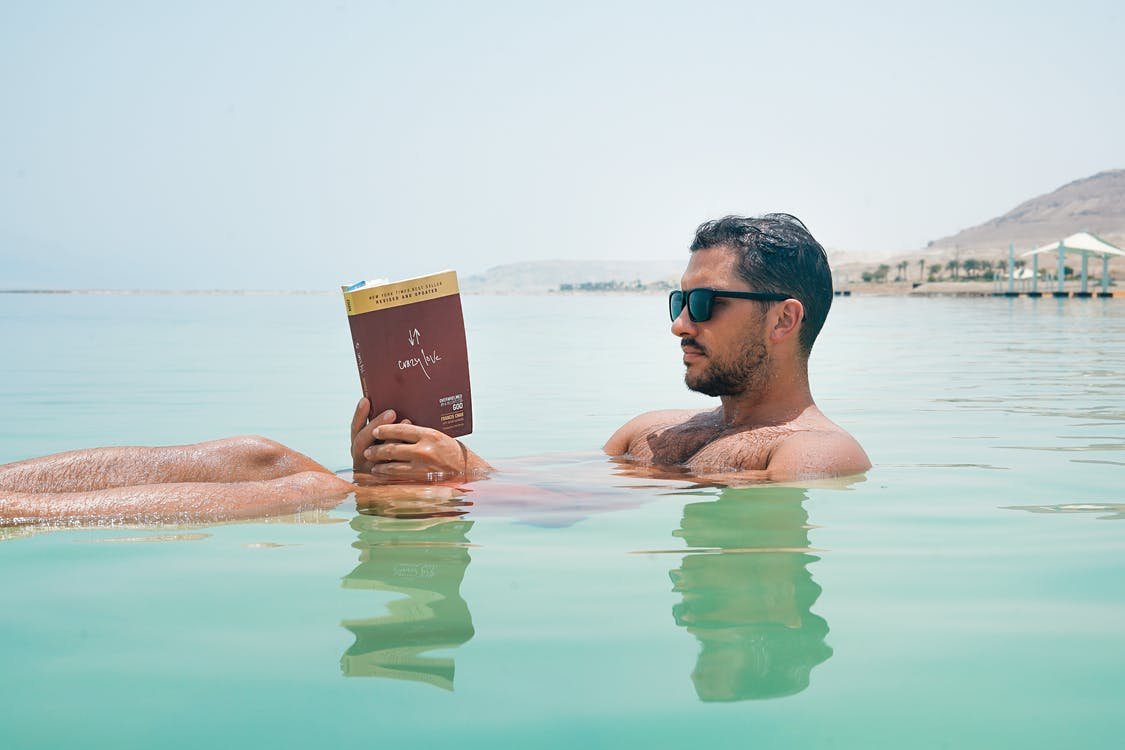 Man Wearing Sunglasses Reading Book on Body of Water