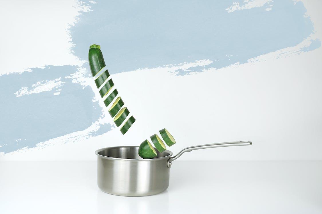 灰色のステンレス鋼のソースパンと緑のキュウリのイラスト
