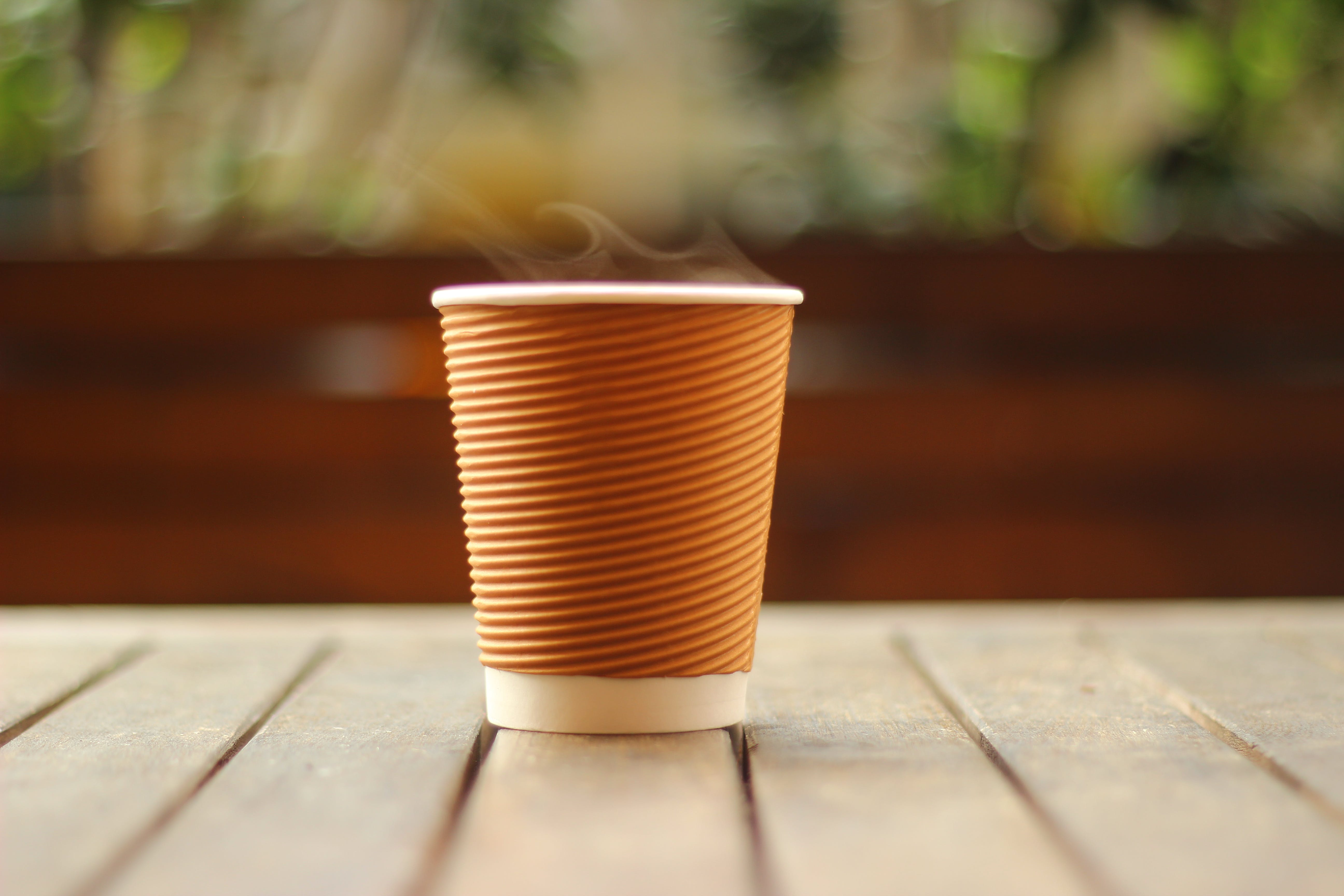 Selective Focus Photo of White and Brown Disposable Cup