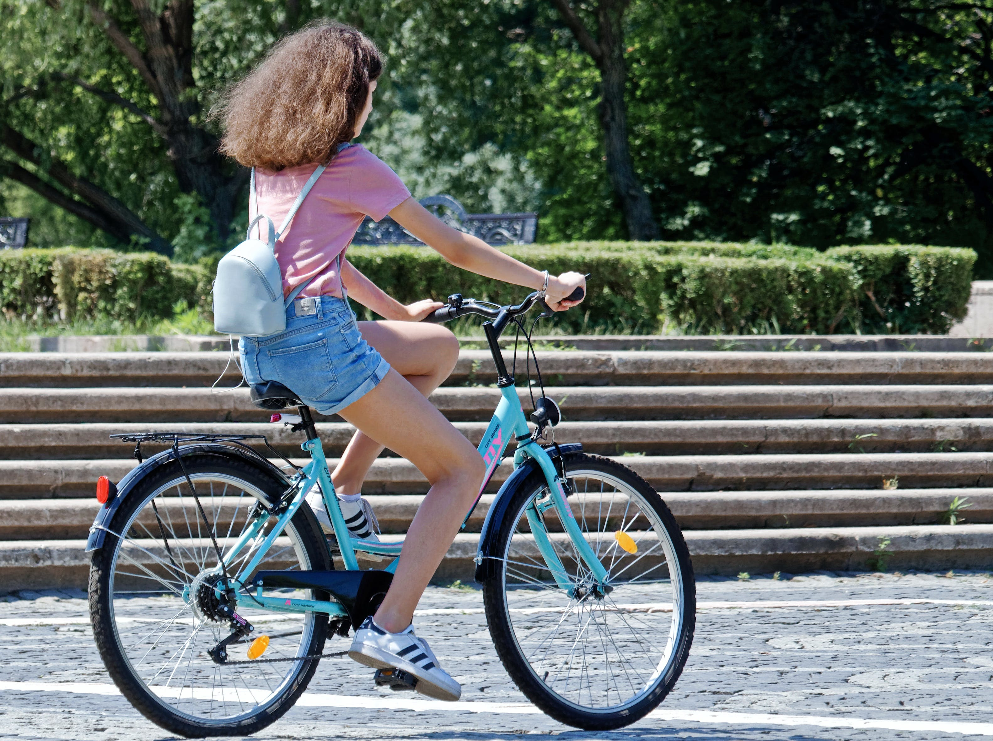 Woman Riding Bicycle Near Concrete Stairs