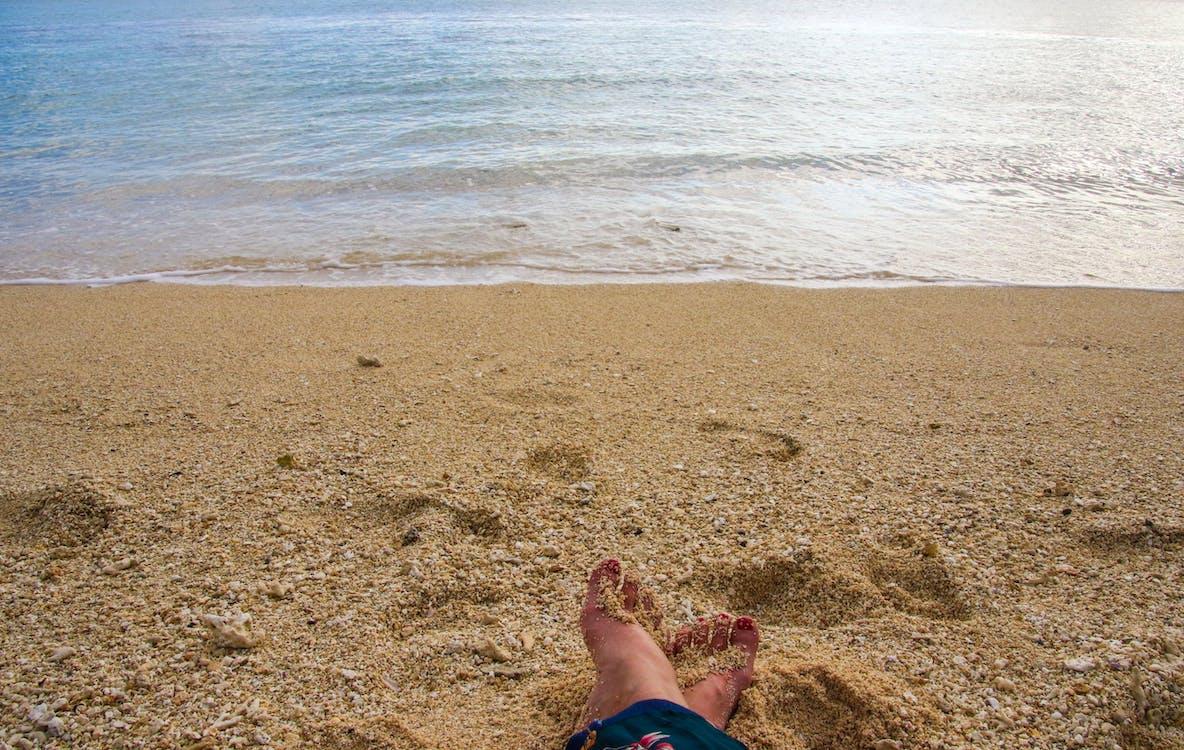 Person Sitting on Seashore