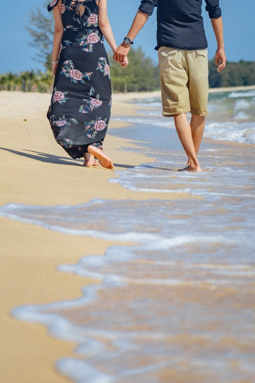 Back view of crop anonymous man in shorts and wristwatch holding hand of barefoot girlfriend in sundress while walking on sandy shore near wavy ocean during honeymoon