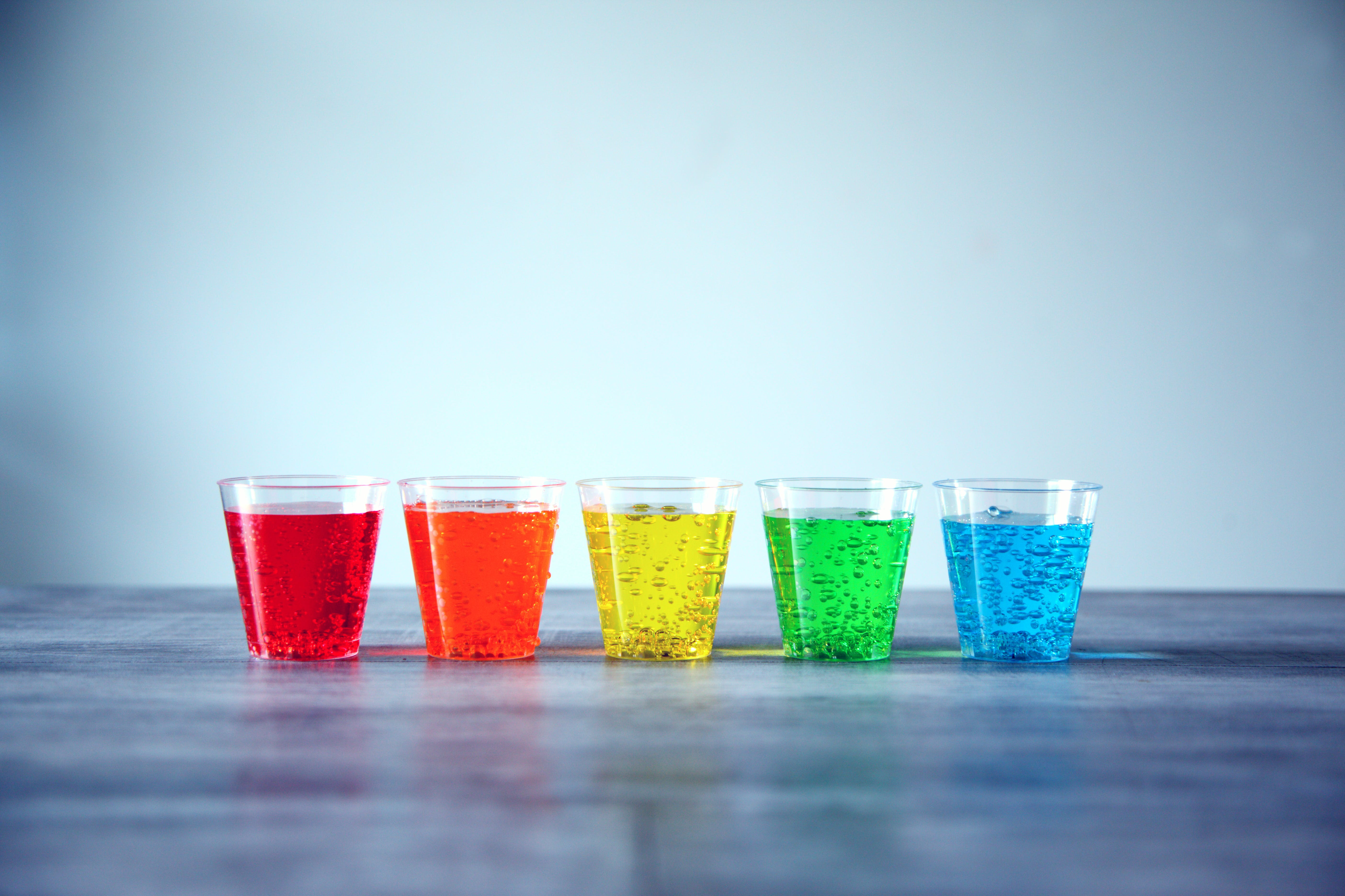 Five Assorted-color Rock's Glasses on Gray Surface