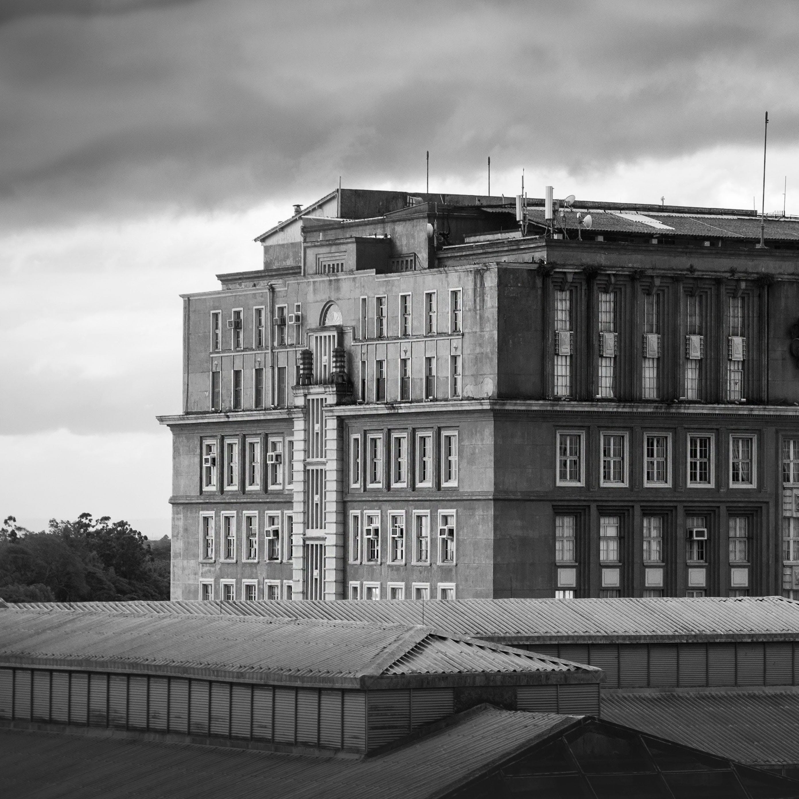 Grayscale Photo of Gray Concrete Building Under the Cloudy Skies