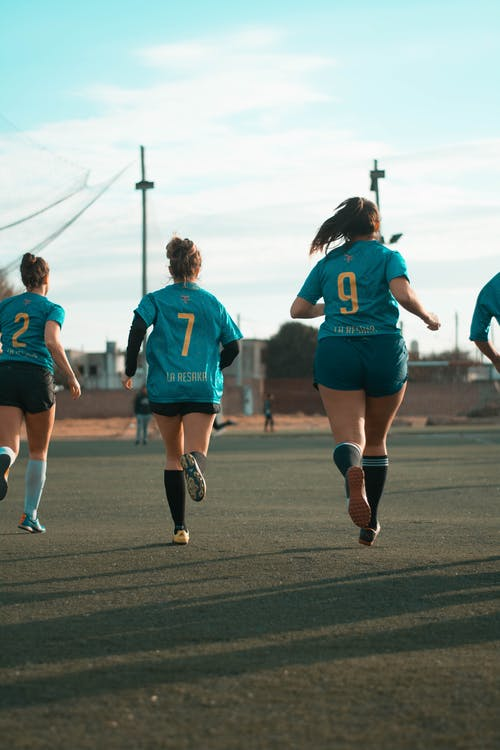 Three Women Wearing Blue Jersey Shirt Running
