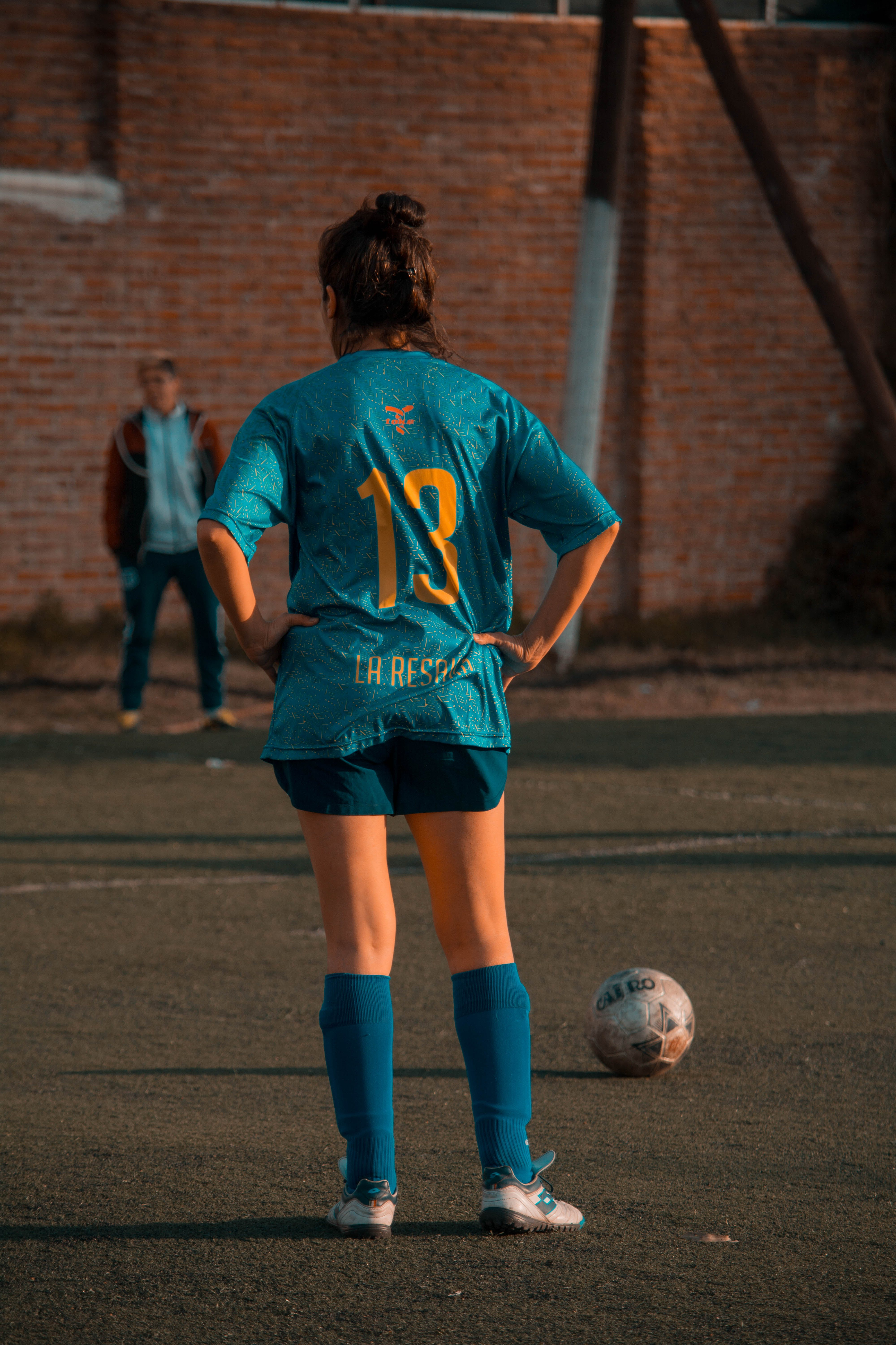 Person In Blue Soccer Jersey Standing In Front Of Ball