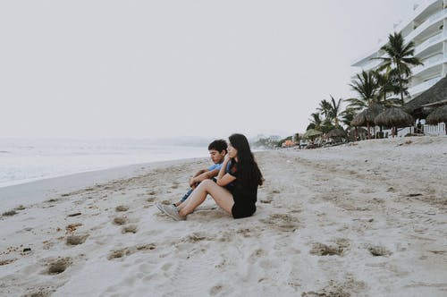 Man And Woman Sitting On Sand