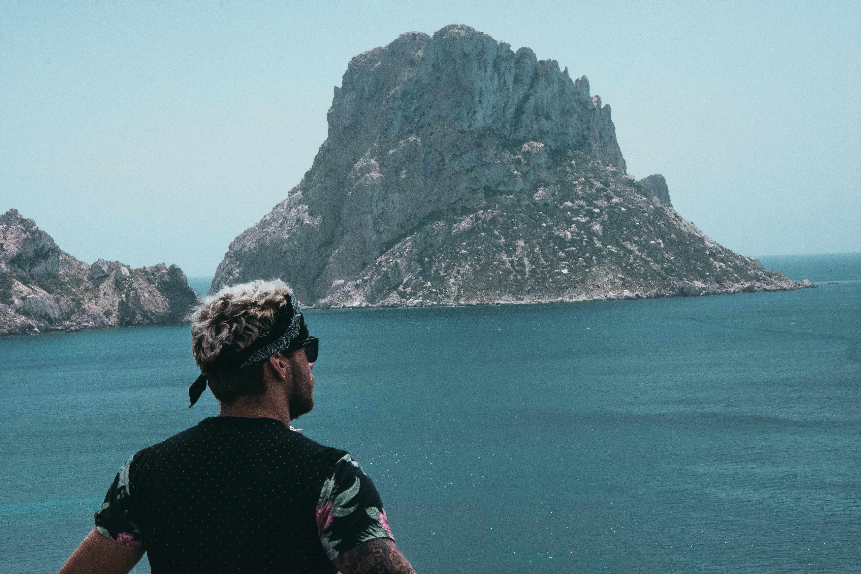 Man Looking at Mountain Across Ocean