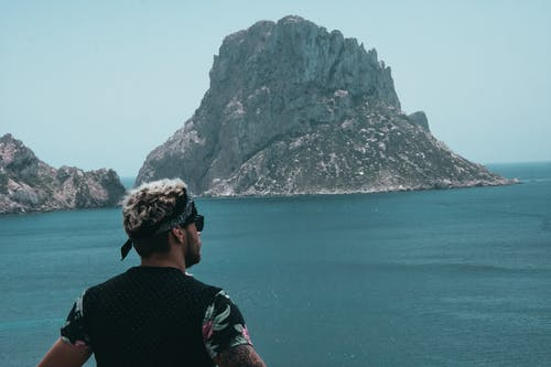 Man Looking at Mountain Across Ocean
